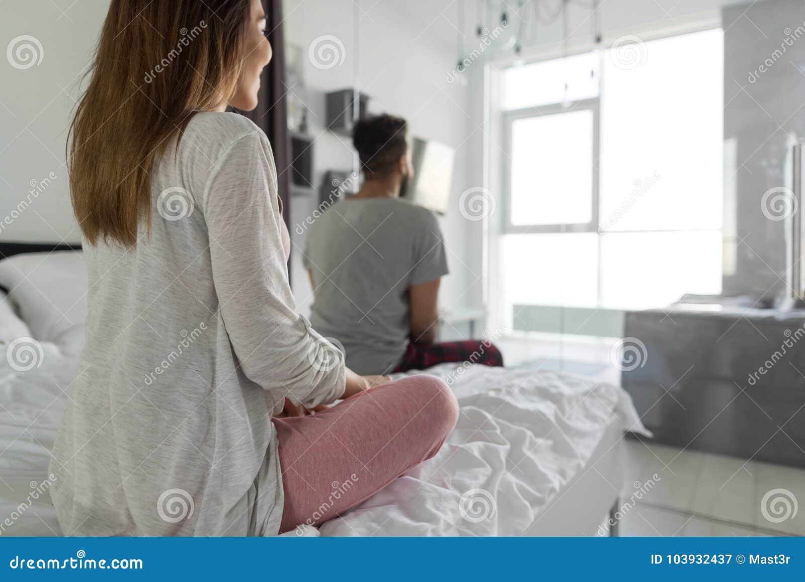 Coppie che si siedono sul letto che guarda nella retrovisione della parte posteriore della - Finestra che si apre ...