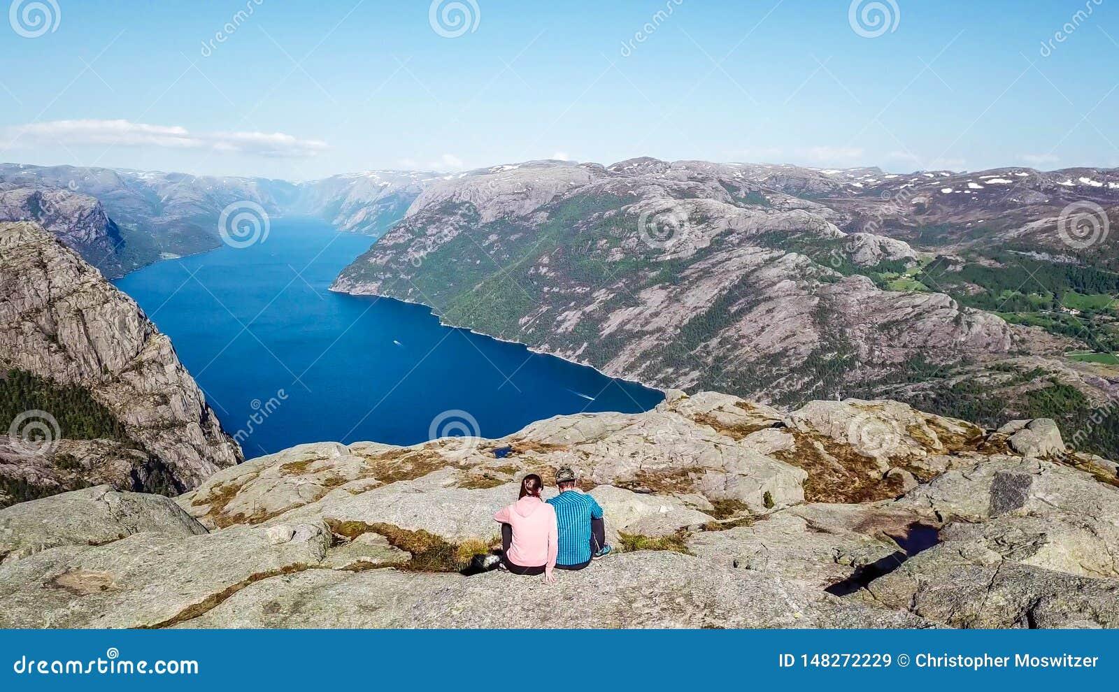Coppie che si siedono sulla roccia che gode della vista del fiordo, vicino a Preikestolen, la Norvegia