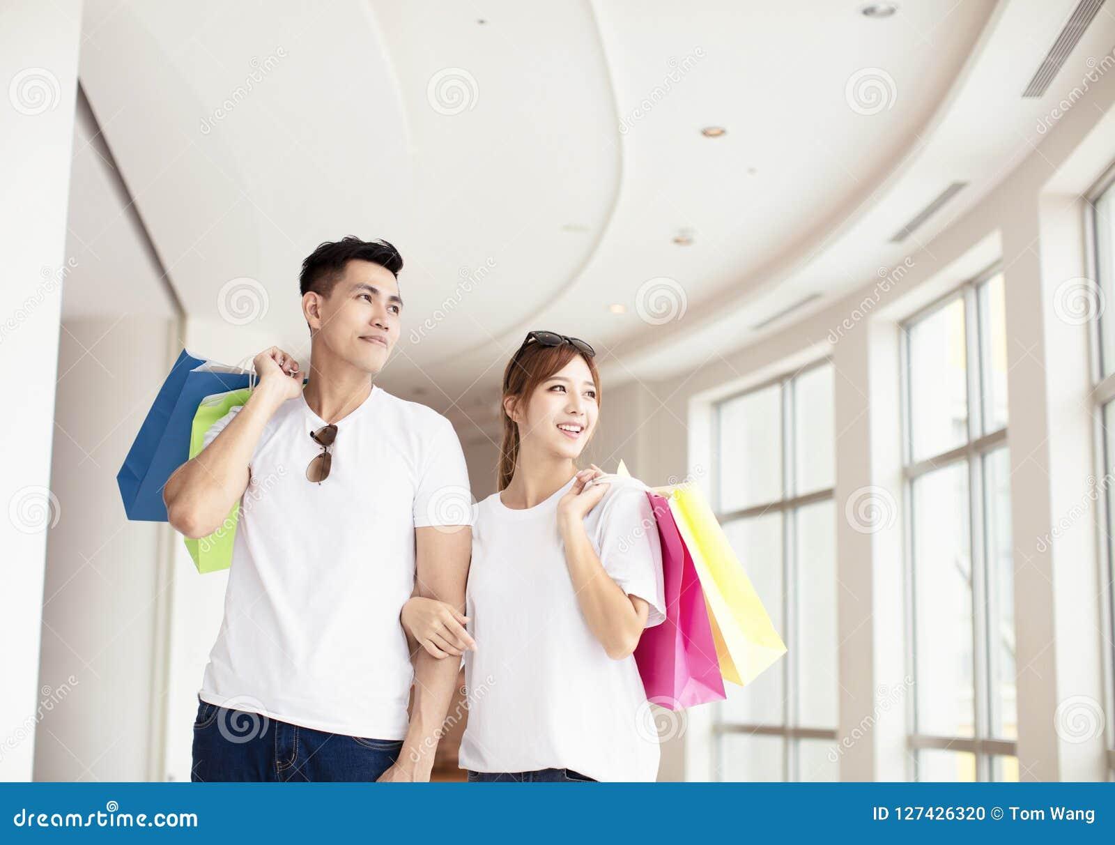 Coppie con i sacchetti della spesa che camminano nel centro commerciale