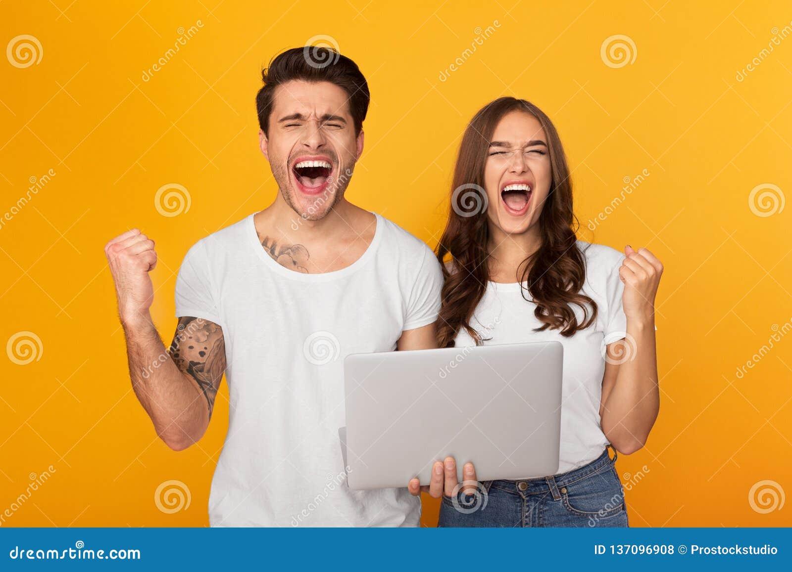 Coppie con il computer portatile che grida e pugni di serraggio come i vincitori