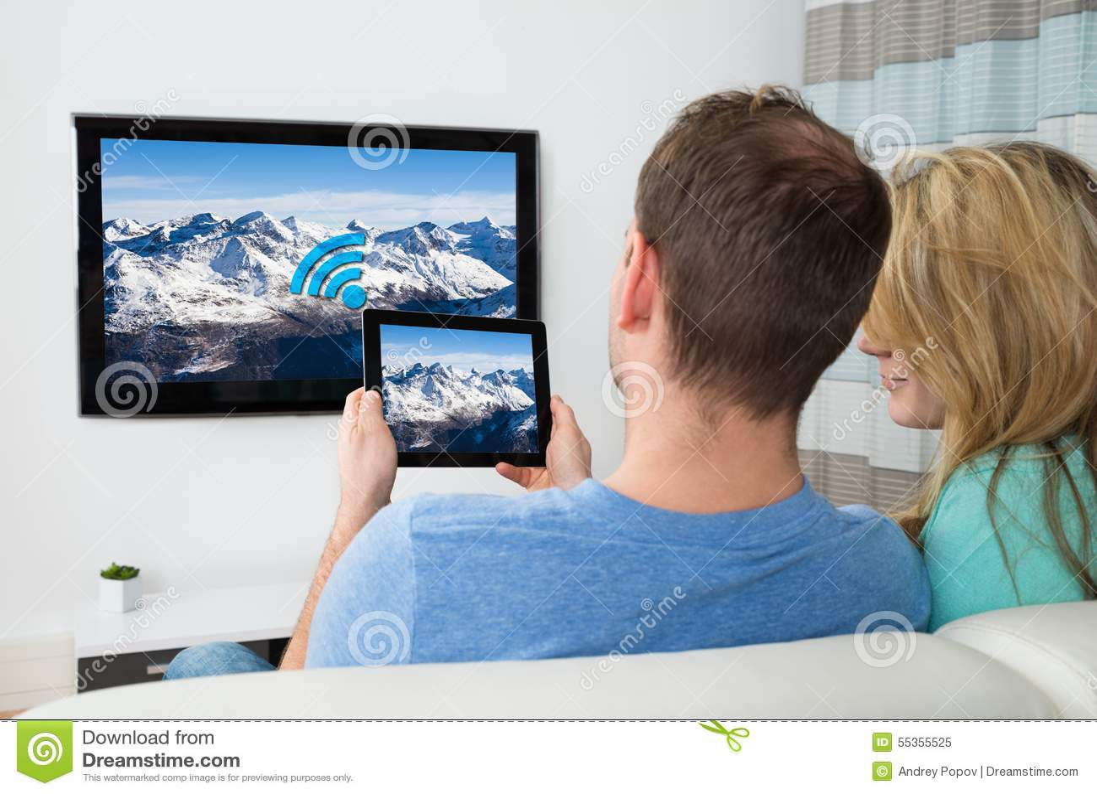 Coppie con la compressa digitale e la televisione nella sala