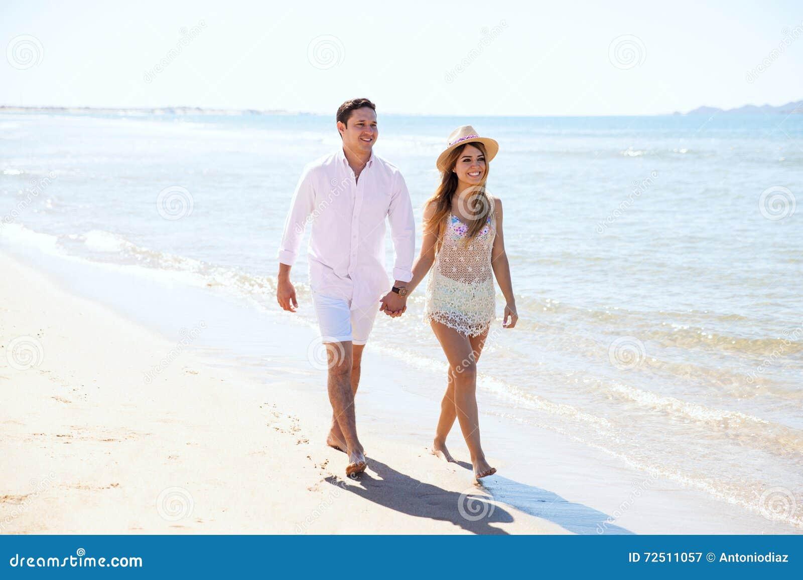 Coppie delle persone appena sposate che camminano giù la spiaggia