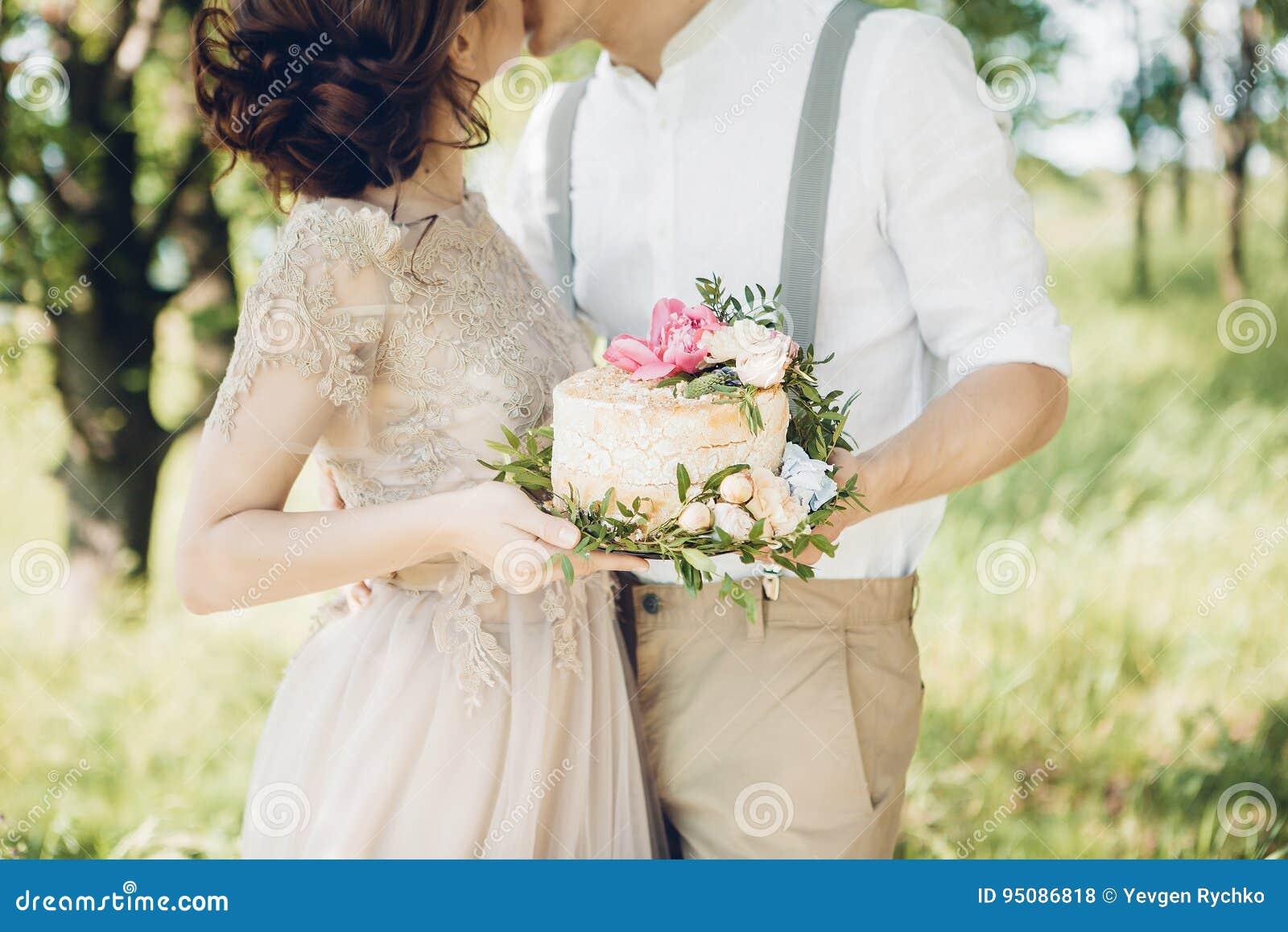 Coppie di nozze sulla natura la sposa e lo sposo con il dolce a nozze