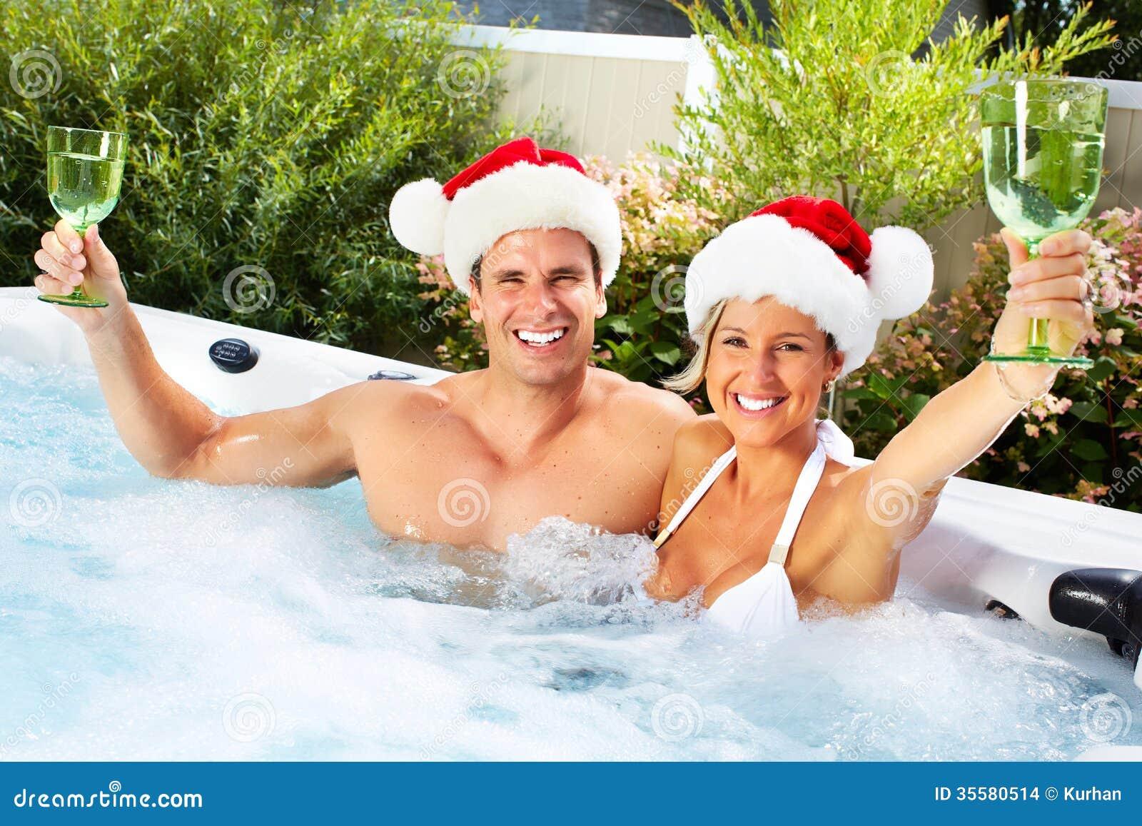 Coppie di Santa di Natale felice in Jacuzzi.