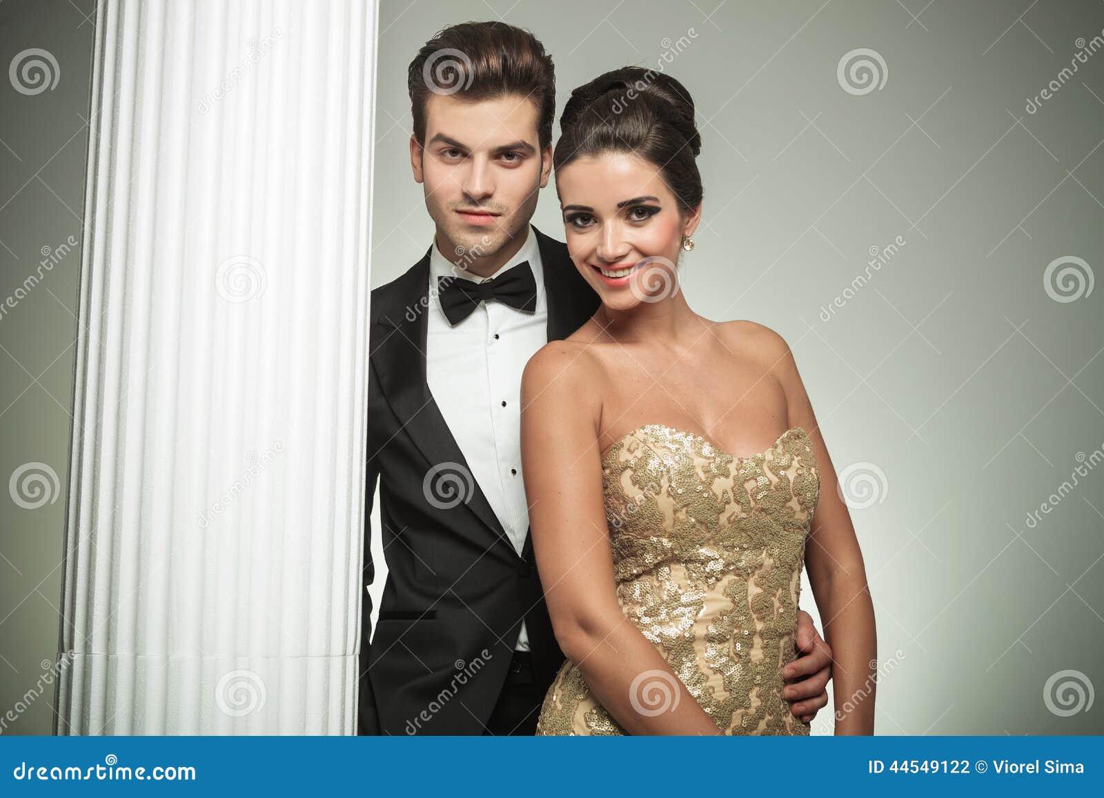 Coppie eleganti di modo che sorridono insieme vicino alla colonna