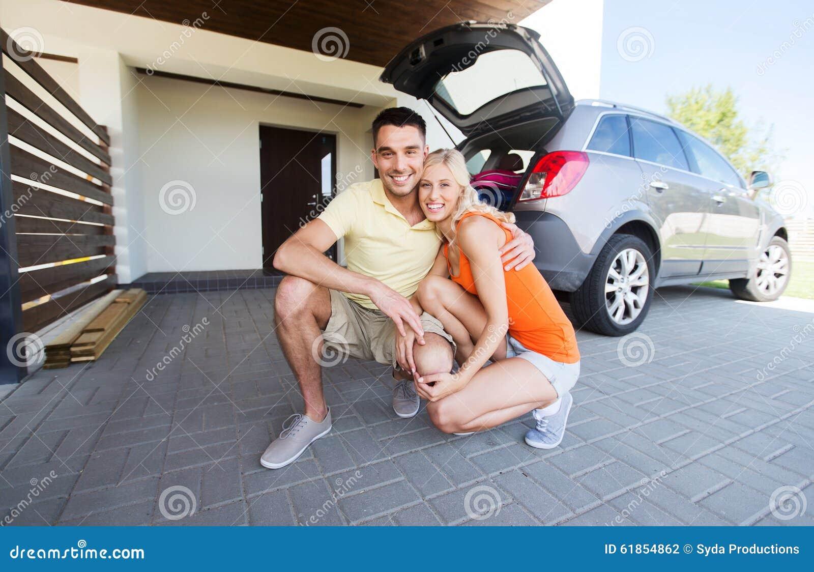 Coppie felici che abbracciano a casa il posto-macchina dell automobile