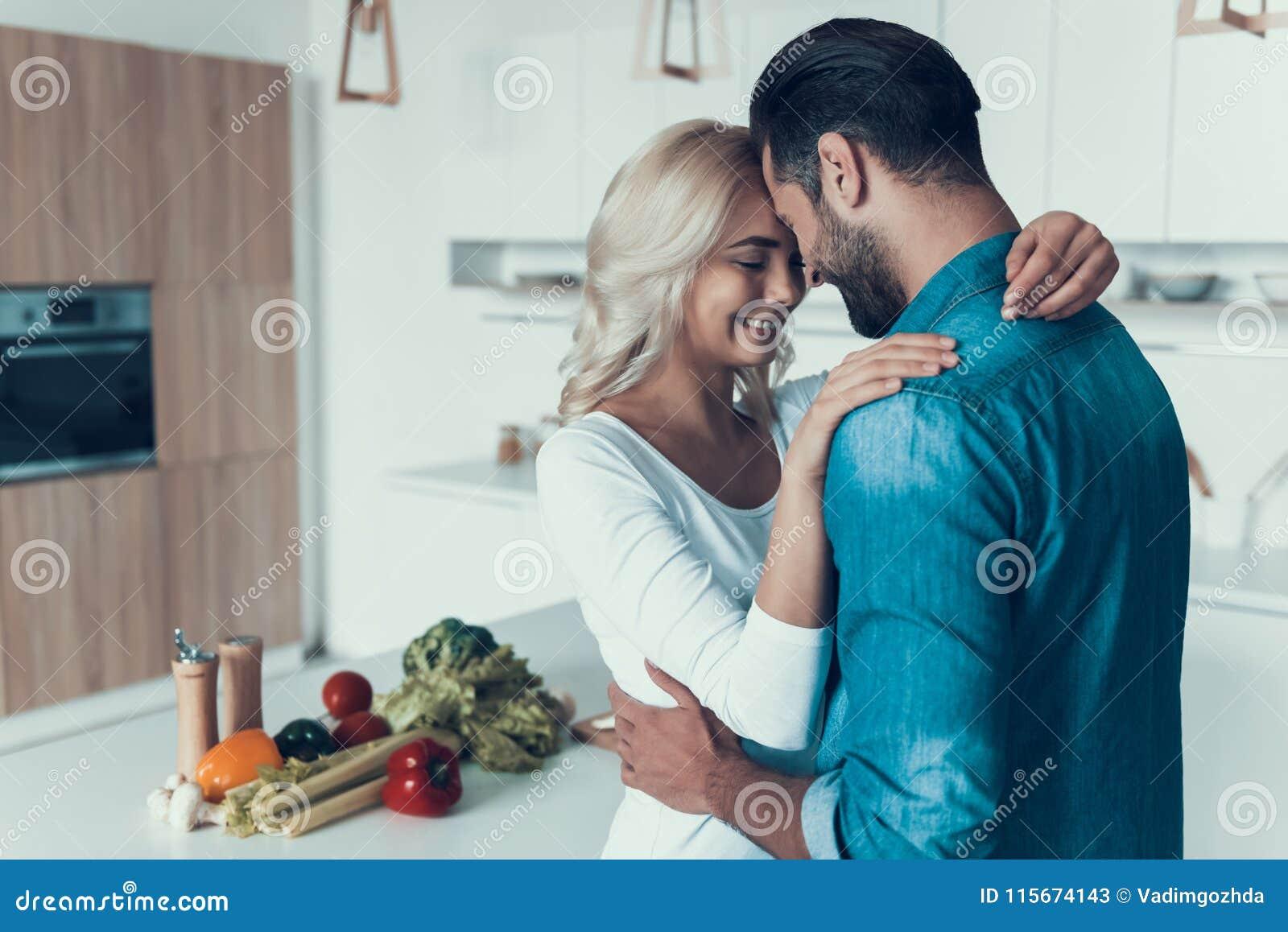 Coppie felici che abbracciano nella cucina Relazione romantica