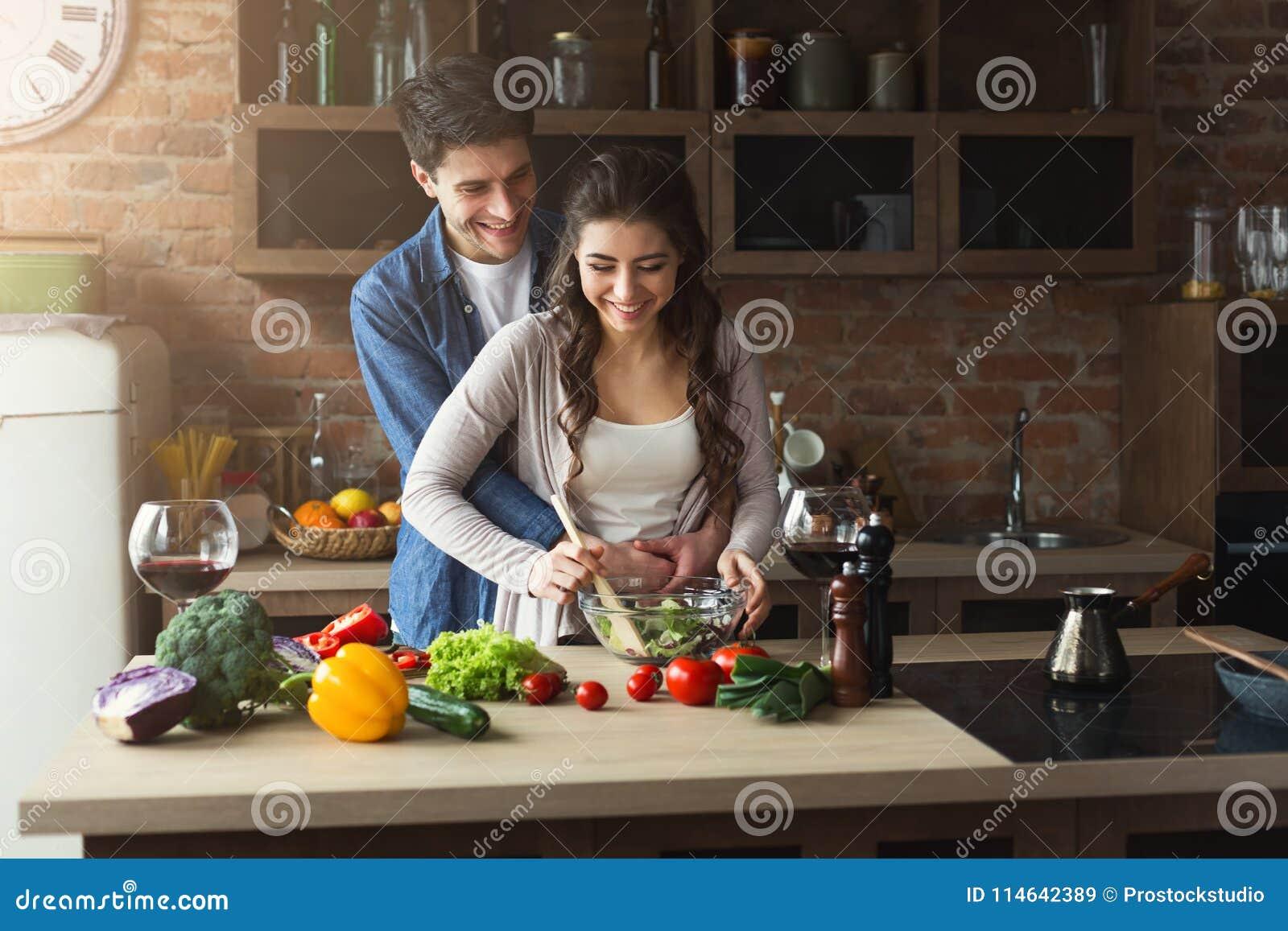 Coppie felici che cucinano insieme alimento sano