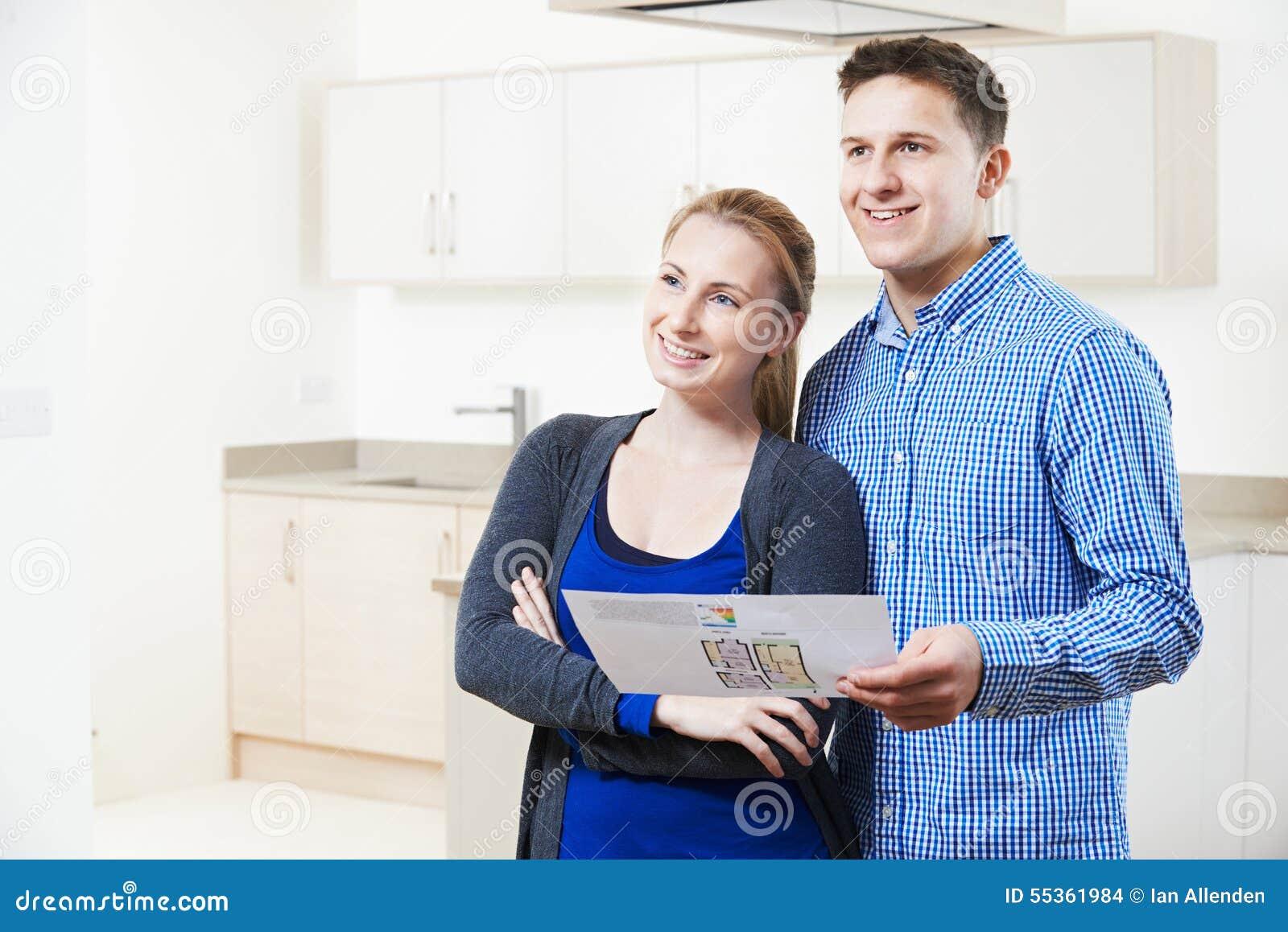 Coppie felici che esaminano i dettagli per la proprietà che sperano di comprare