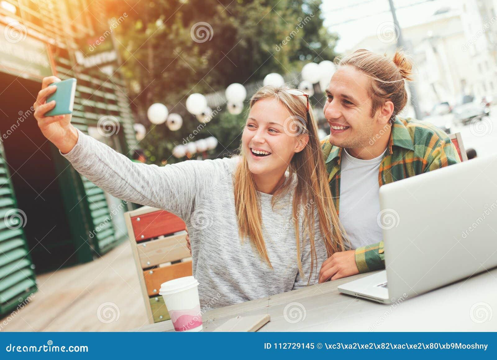 Coppie felici che prendono selfie mentre sedendosi in caffè all aperto