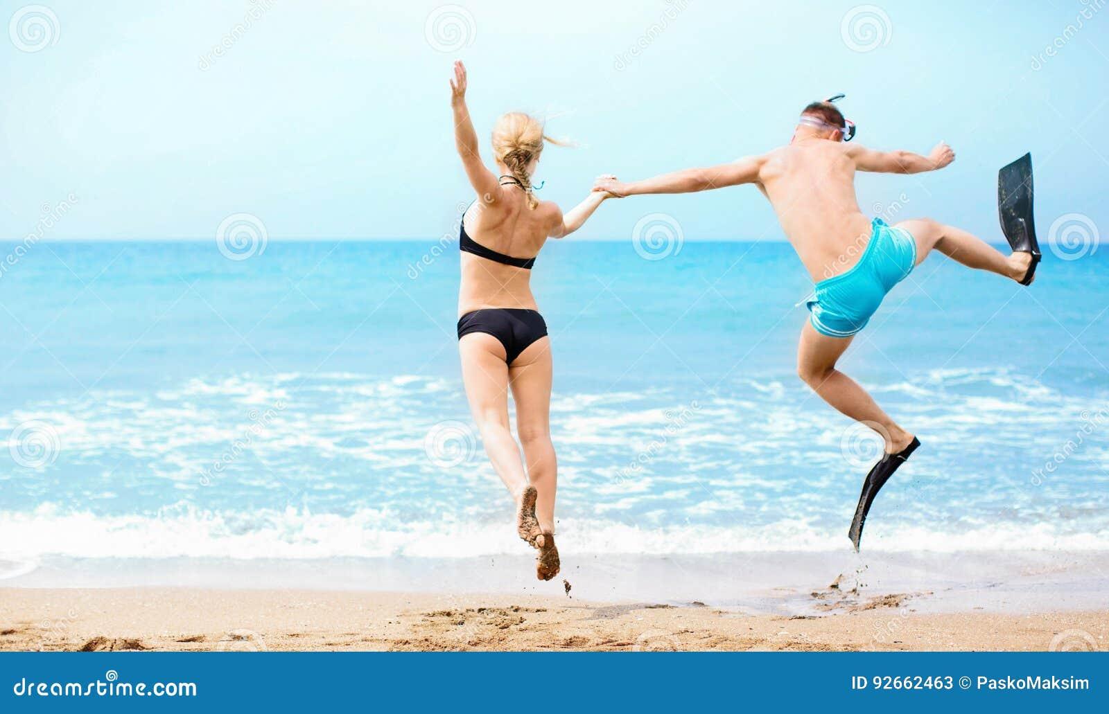 Coppie felici che saltano nel mare