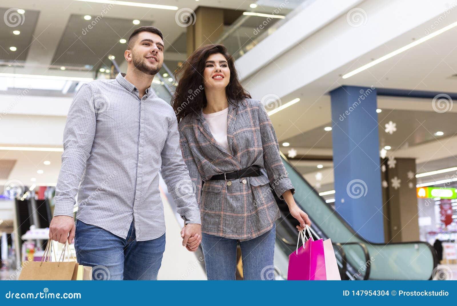 Coppie felici con i sacchetti della spesa che camminano nel centro commerciale