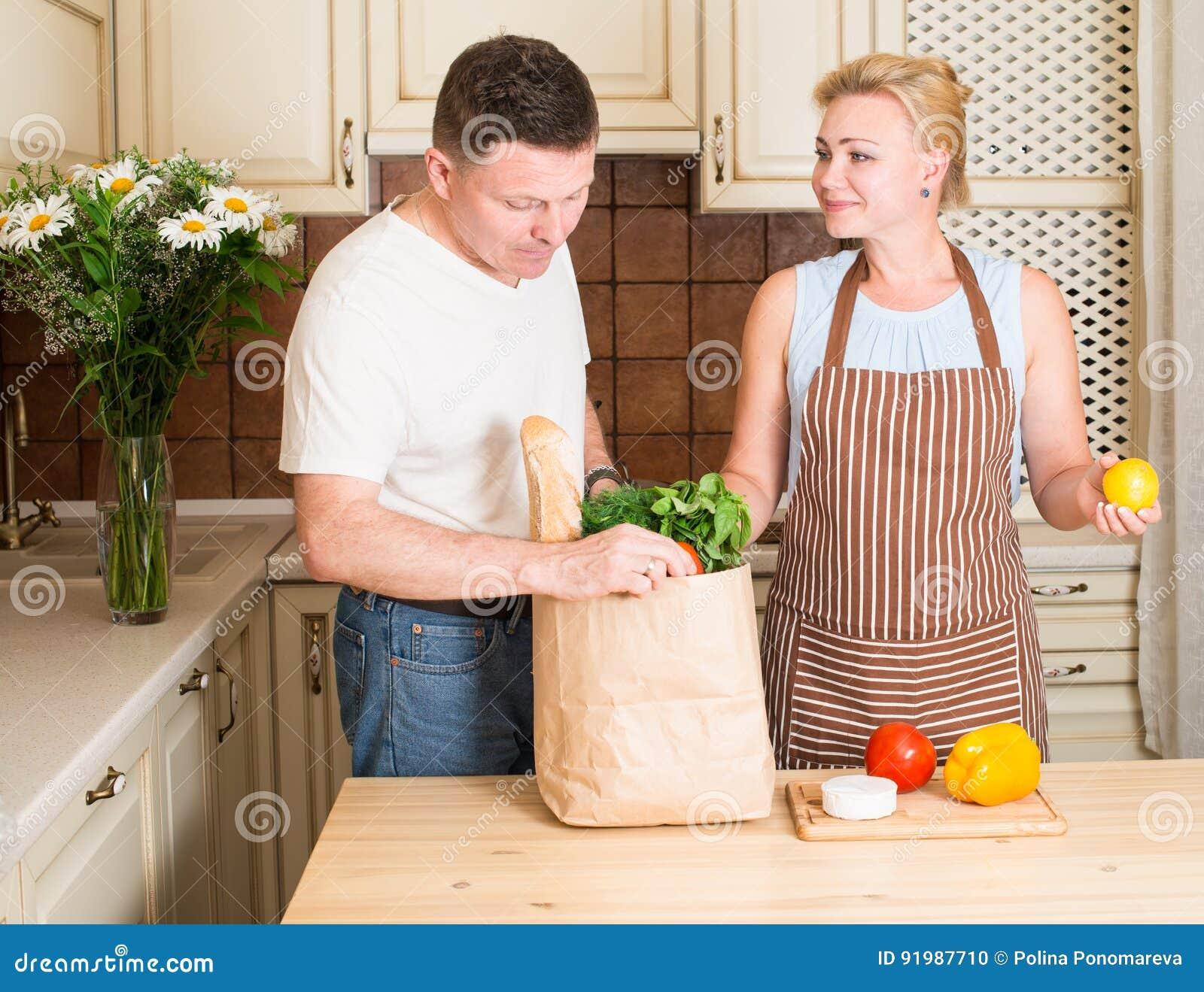 Coppie felici con il sacco di carta della drogheria con le verdure in cucina