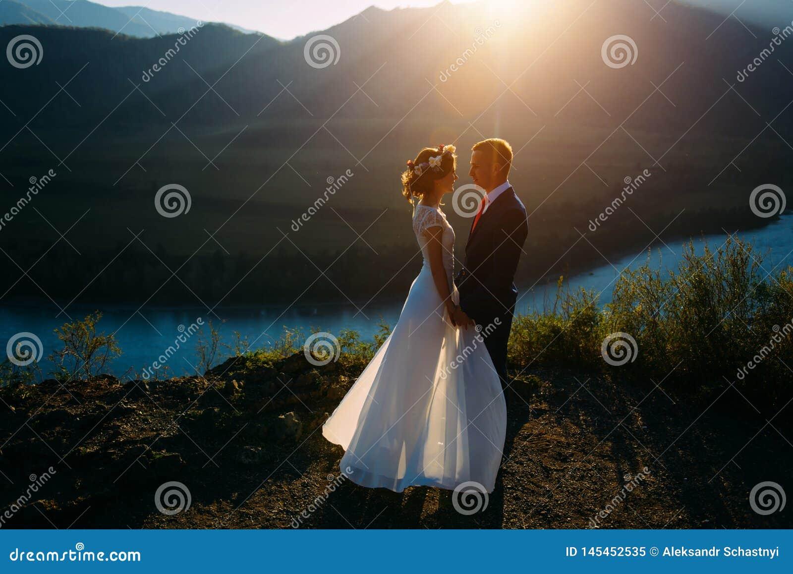 Coppie felici di nozze che restano il bello paesaggio con le montagne