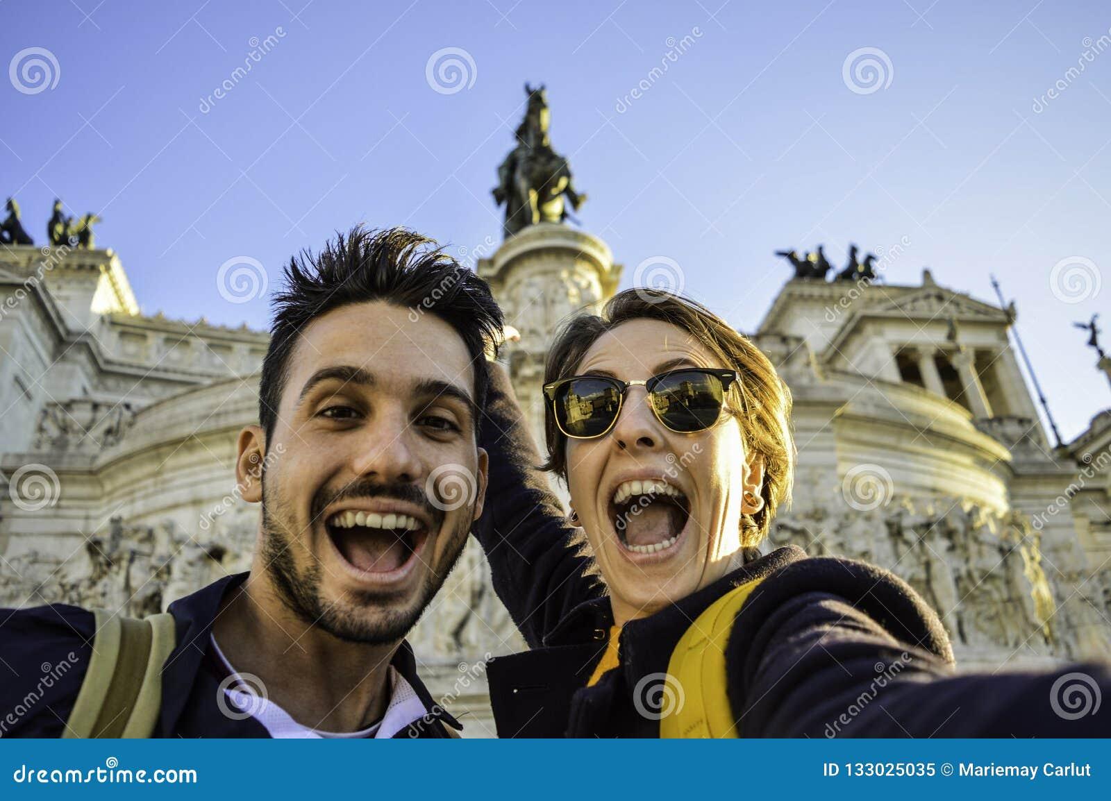 Coppie felici di viaggio che prendono selfie con lo smartphone in punto di riferimento famoso nella piazza Venezia, Roma, Italia