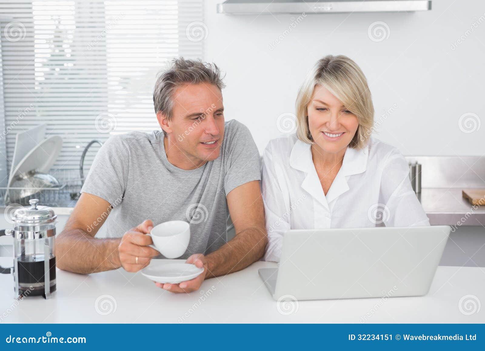 Coppie felici facendo uso del computer portatile di mattina