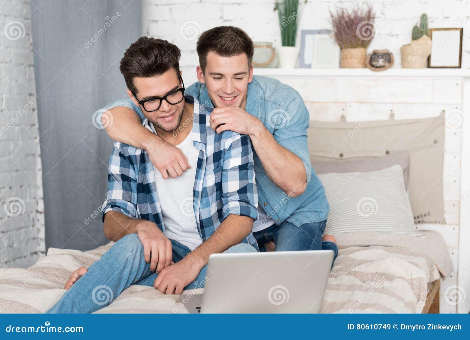 Gay A Letto.Coppie Gay Che Si Siedono Sul Letto E Che Per Mezzo Di Un Computer