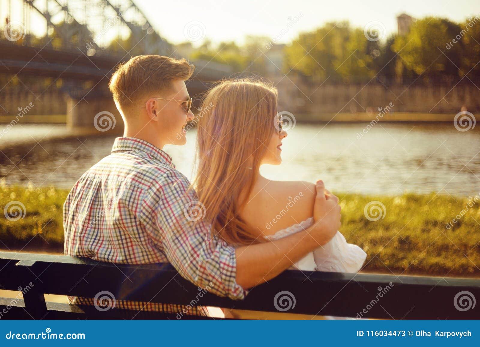 Coppie giovani belle che si siedono su un banco nel parco vicino al fiume Le coppie romantiche su un banco dal fiume hanno una da