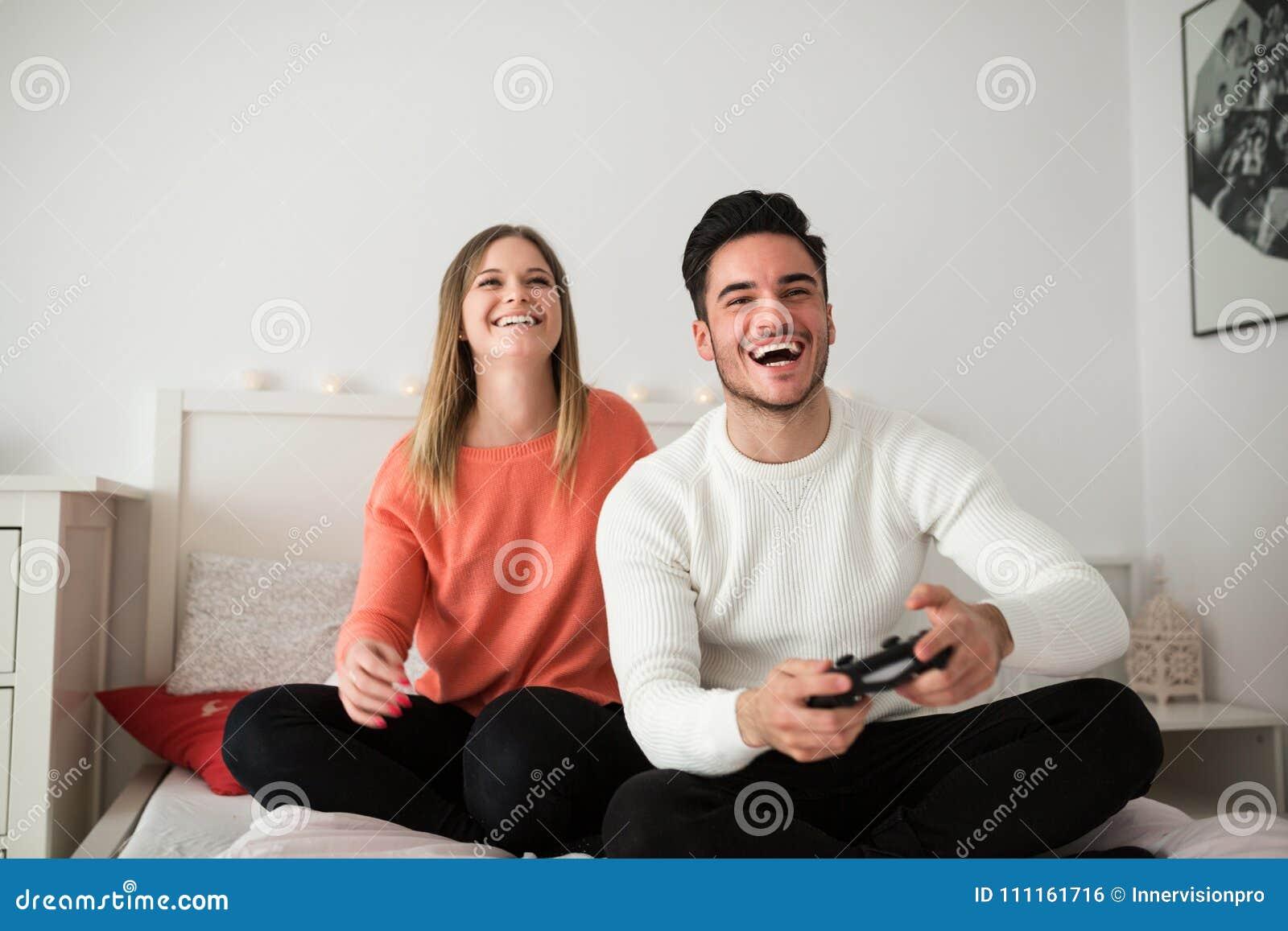 Coppie giovani che giocano i video giochi a letto fotografia stock immagine di ragazza - Giochi che si baciano a letto ...