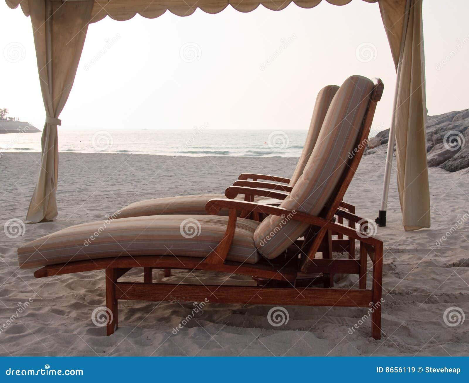 Coppie i loungers del sole sulla spiaggia