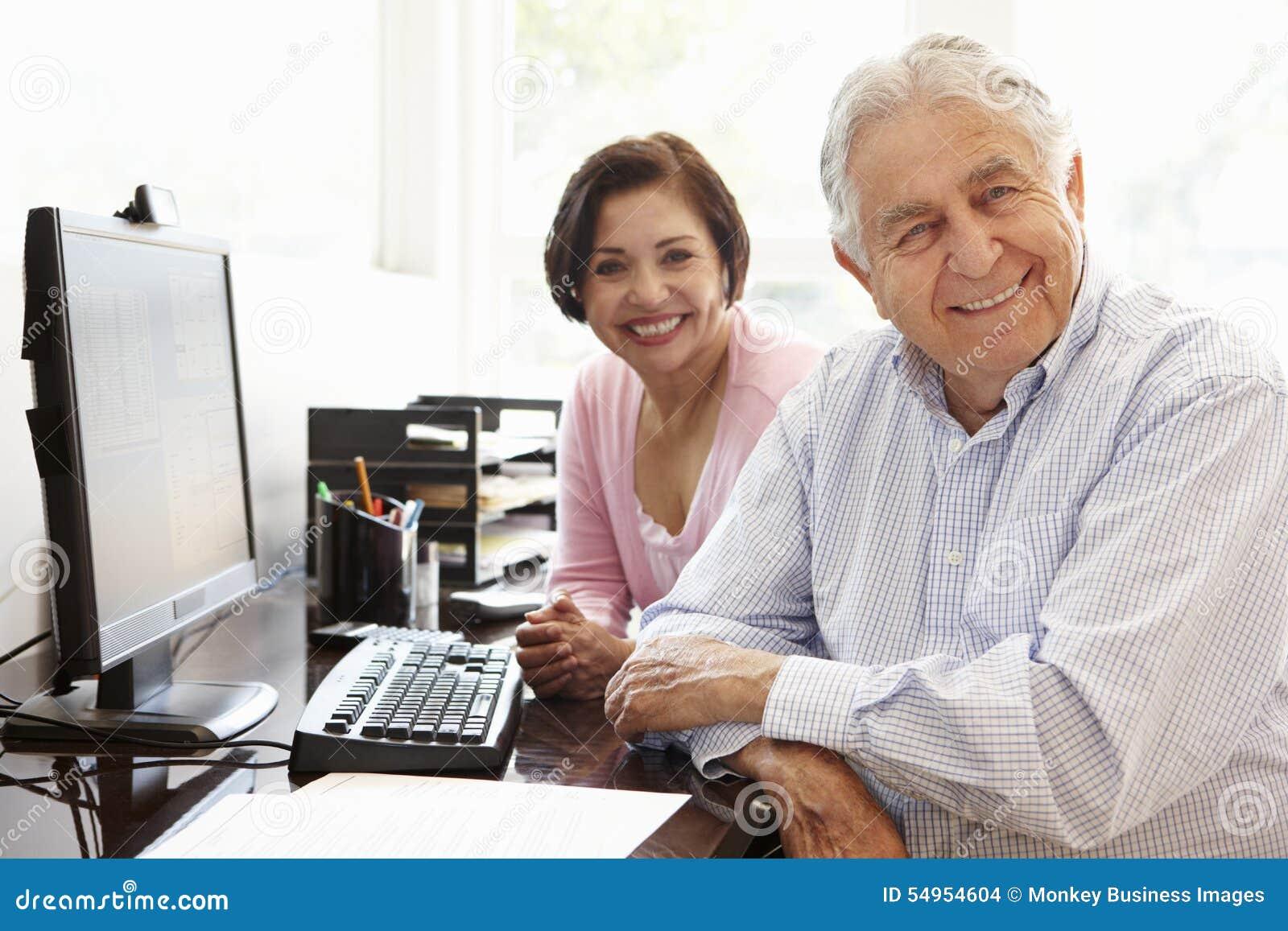 Coppie ispane senior che lavorano al computer a casa