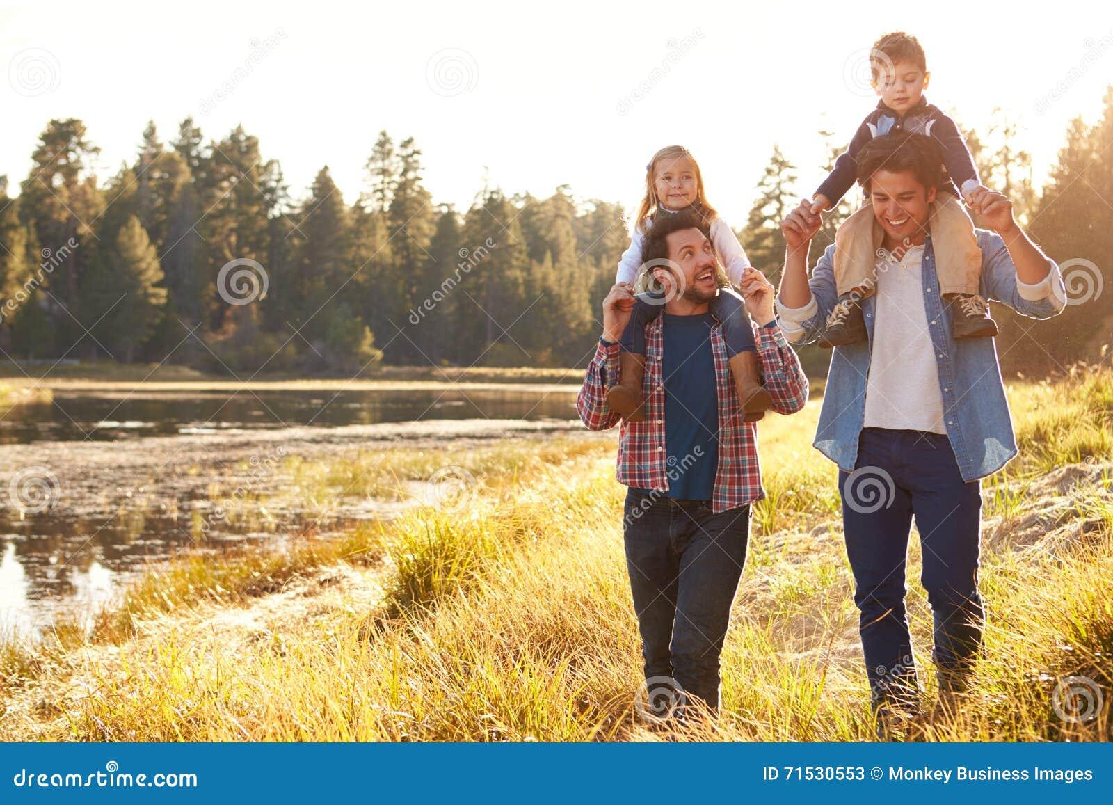Coppie maschii gay con i bambini che camminano dal lago