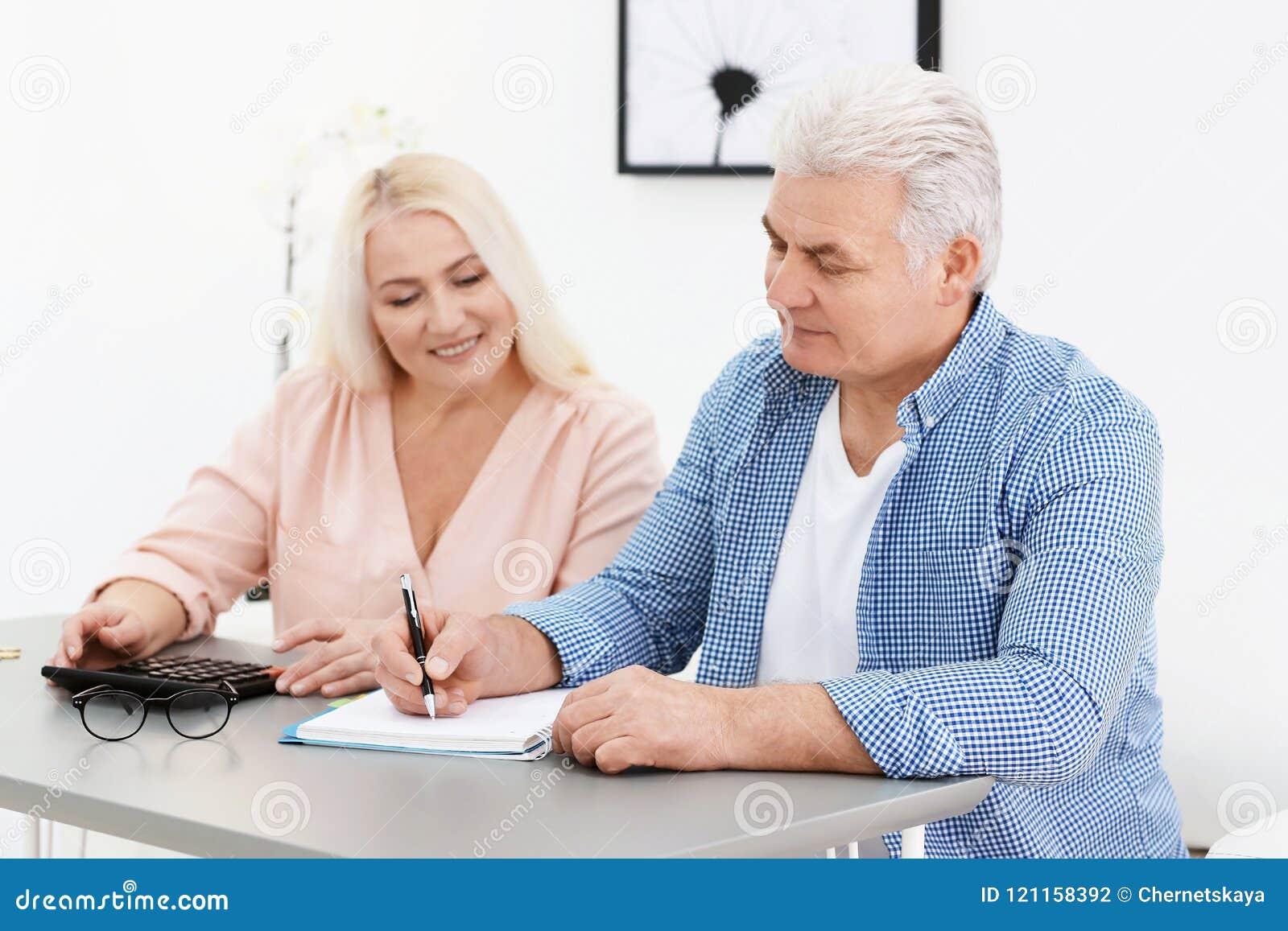 Coppie mature che pensano sopra il pagamento di pensione
