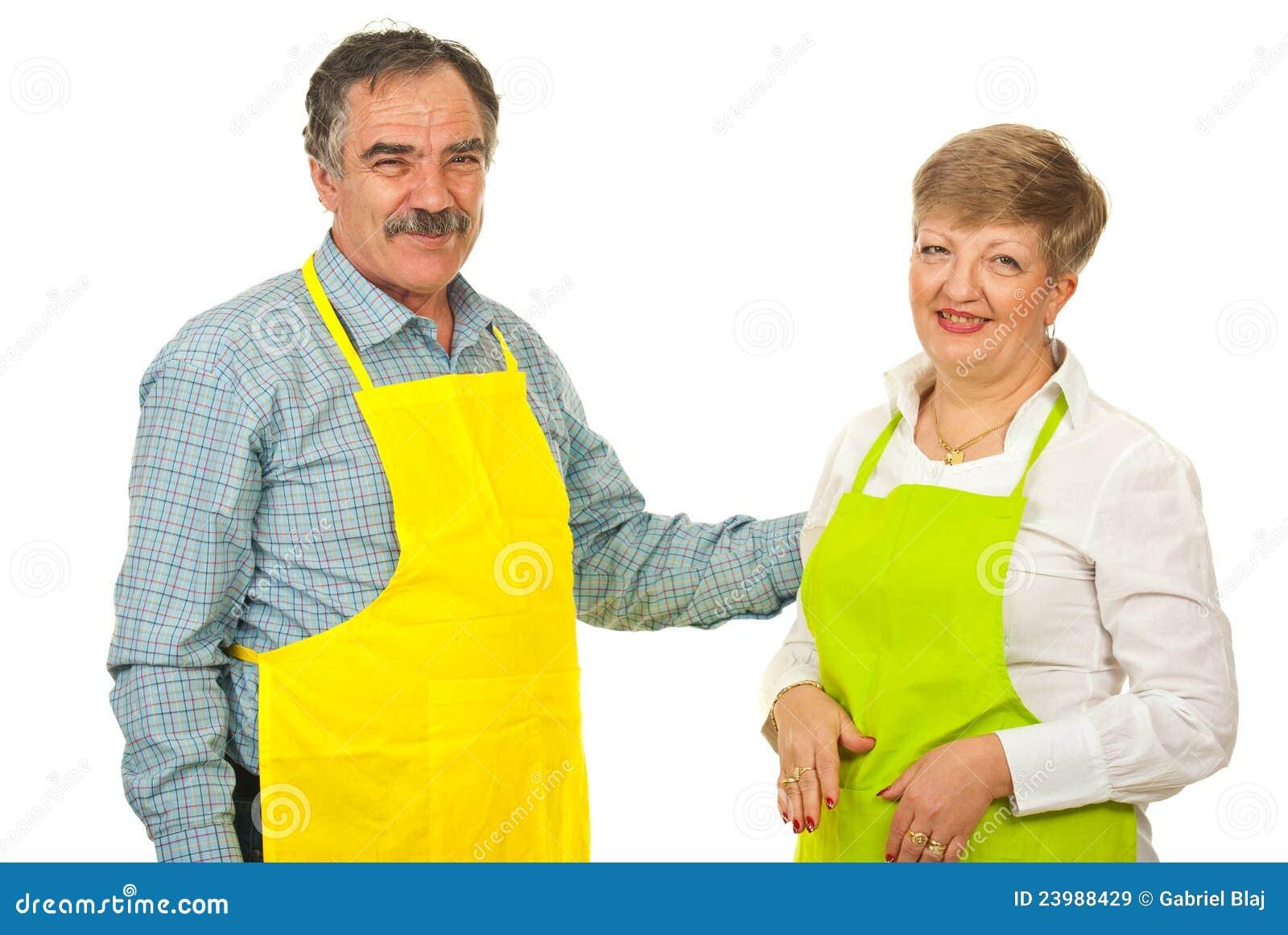 Coppie mature felici con i grembiuli