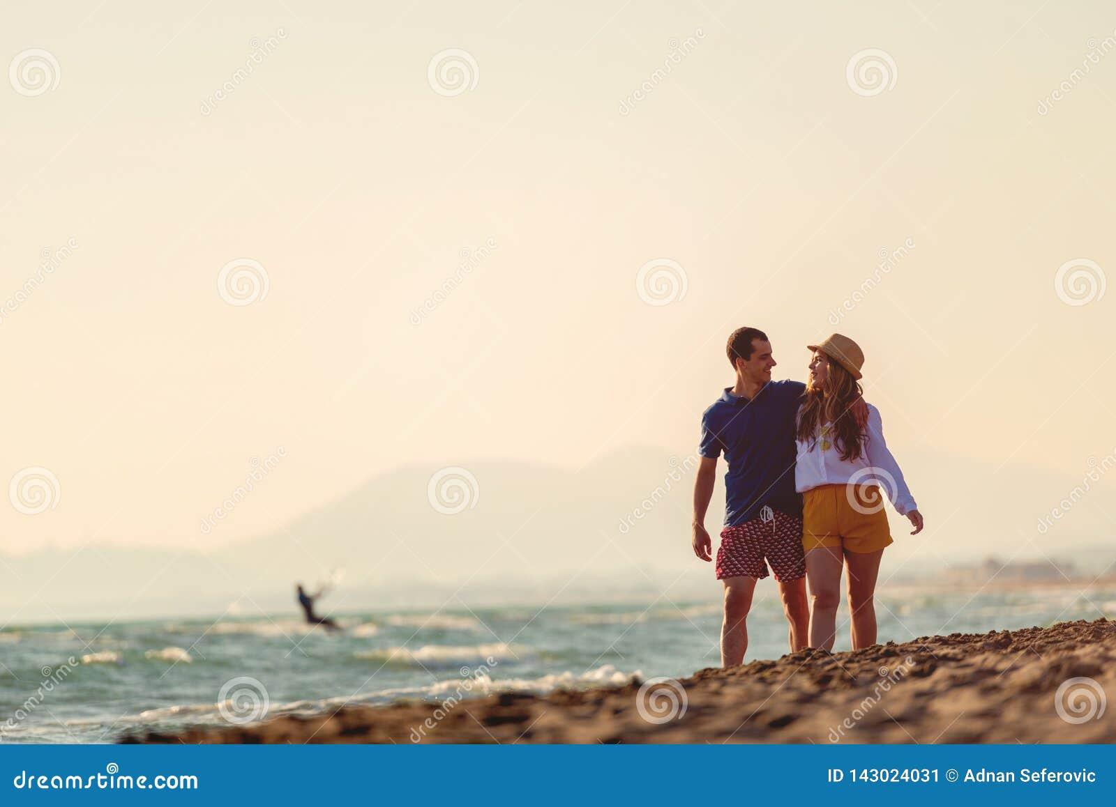 Coppie Medio Evo romantico felice che godono di bella passeggiata di tramonto sulla spiaggia