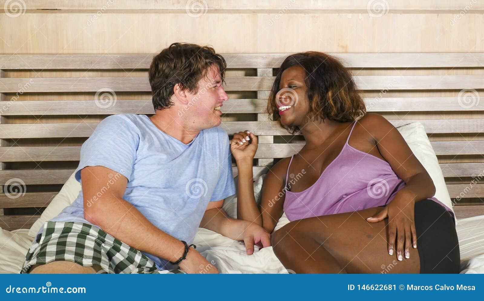 Coppie miste di etnia nell amore che stringe a s? insieme a casa a letto con la donna americana del bello africano nero allegro e