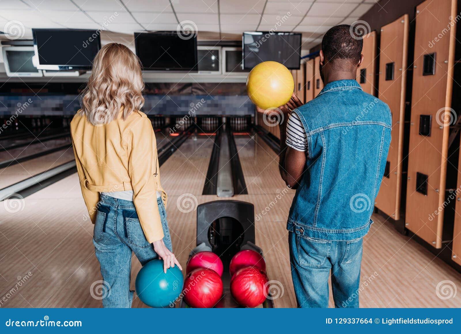 Coppie multietniche con le palle da bowling che stanno davanti ai vicoli