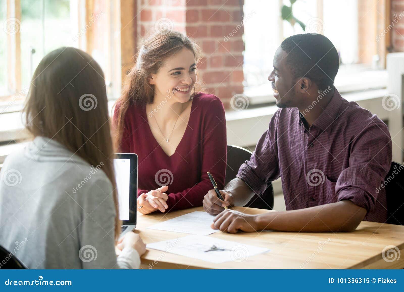 Coppie multietniche felici che se esaminano prima della firma del co