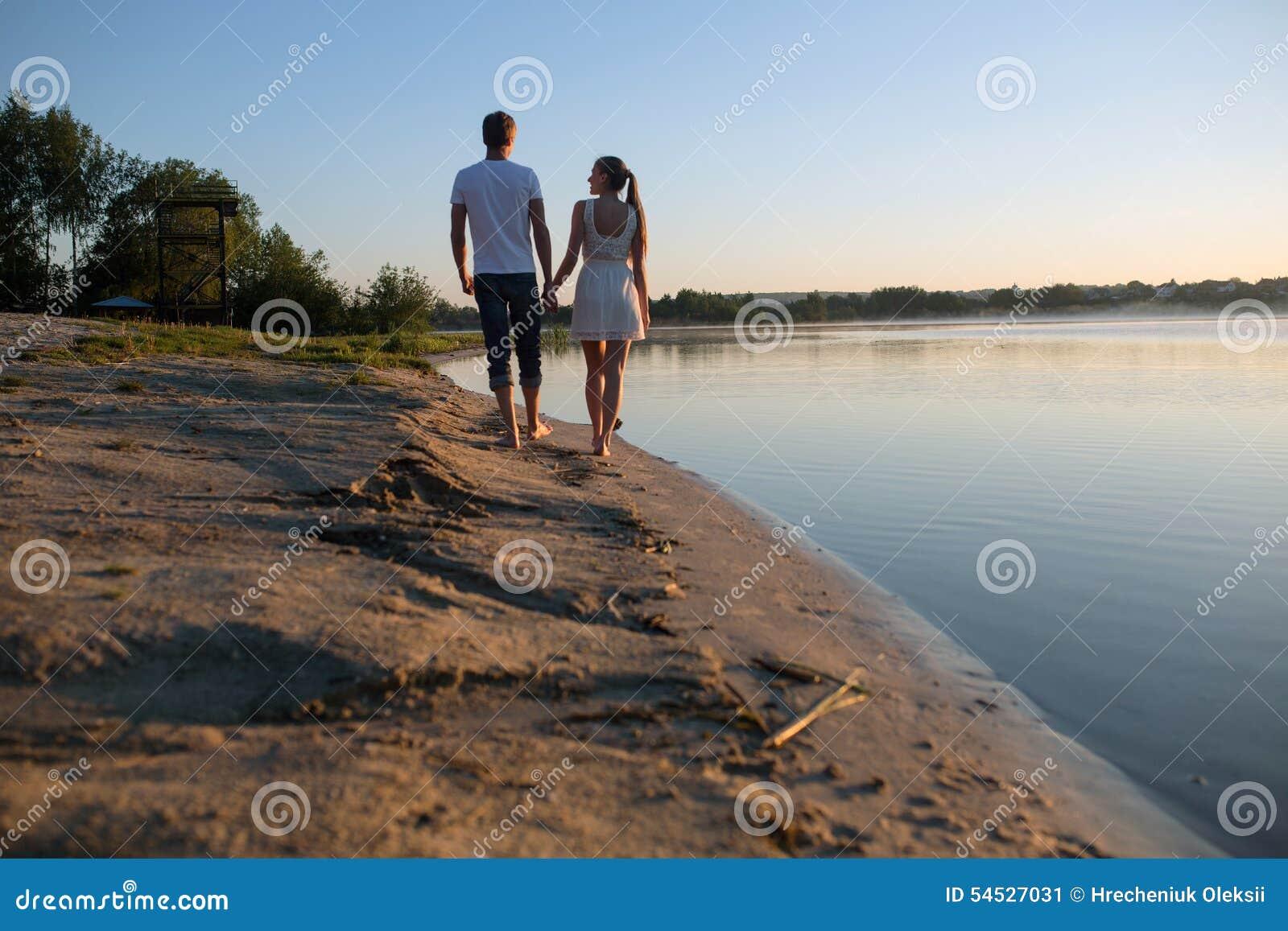 Coppie nell alba sulla spiaggia