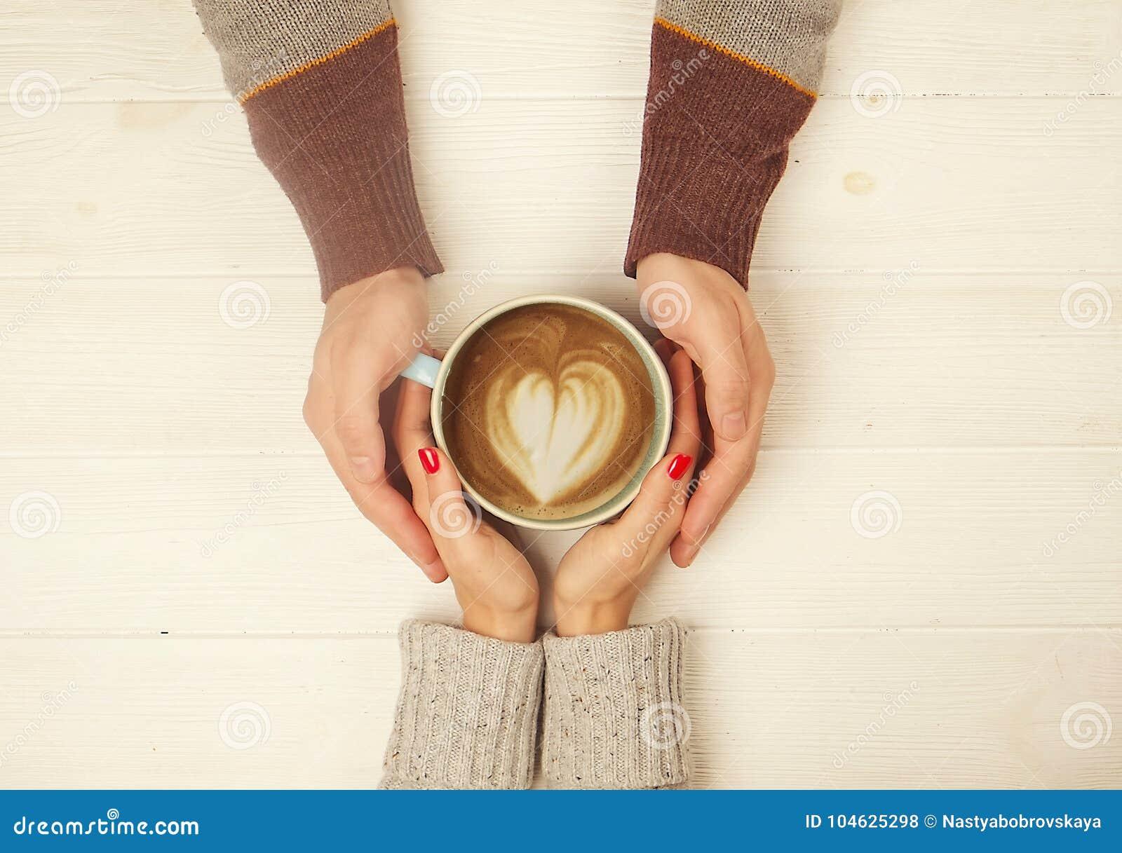 Coppie nell amore che si tiene per mano con la tazza dell immagine di vista superiore del coffe su fondo di legno bianco L uomo t