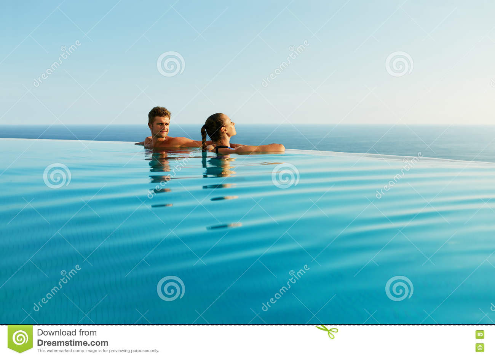 Coppie nell amore nello stagno della località di soggiorno di lusso sulle vacanze estive romantiche