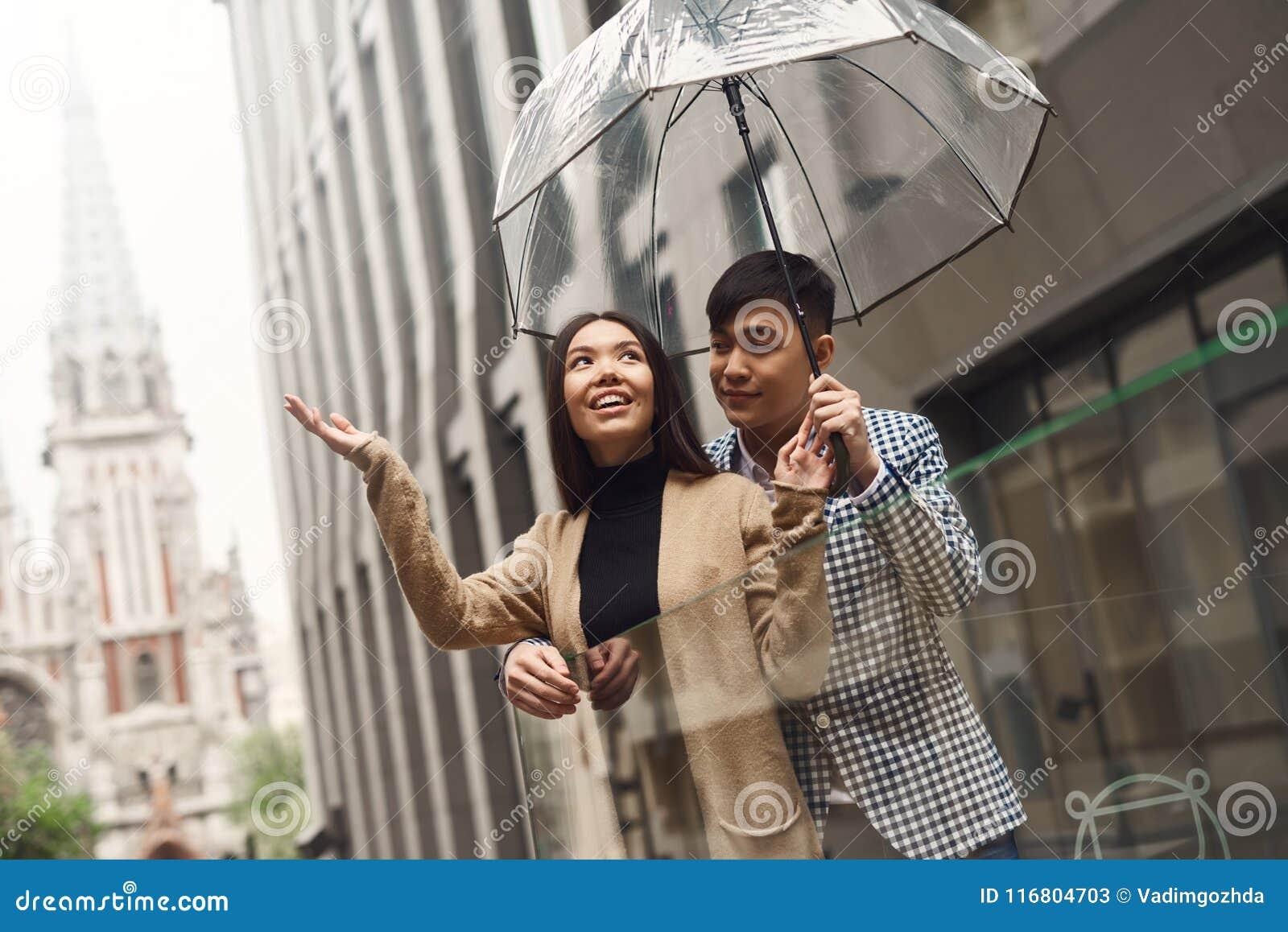 Coppie nell amore sotto l ombrello nel fondo del centro commerciale