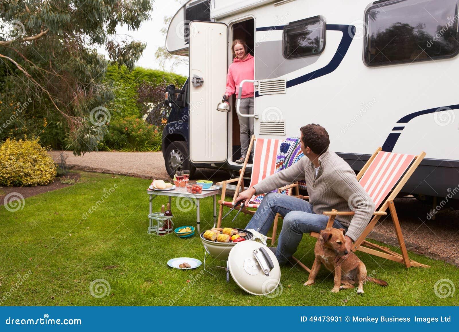 Coppie nella festa di Van Enjoying Barbeque On Camping