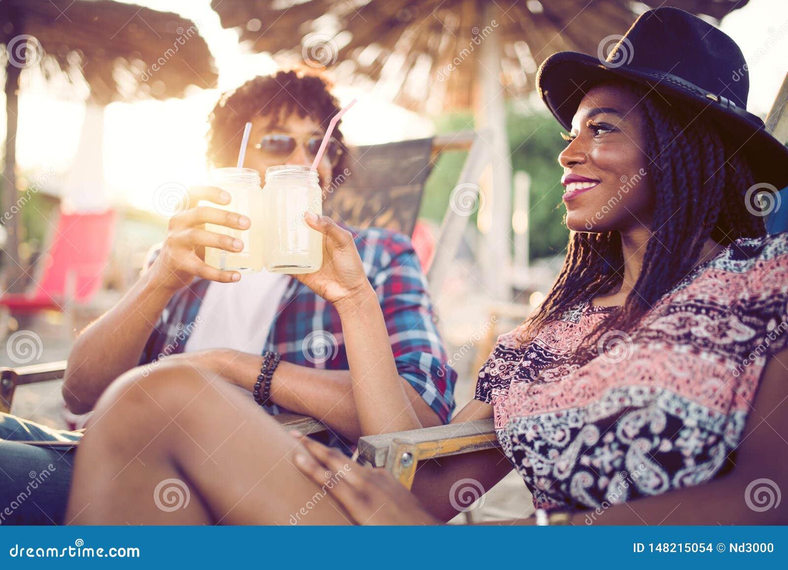 Coppie nere felici sulla spiaggia mentre rilassandosi sui loro sdrai