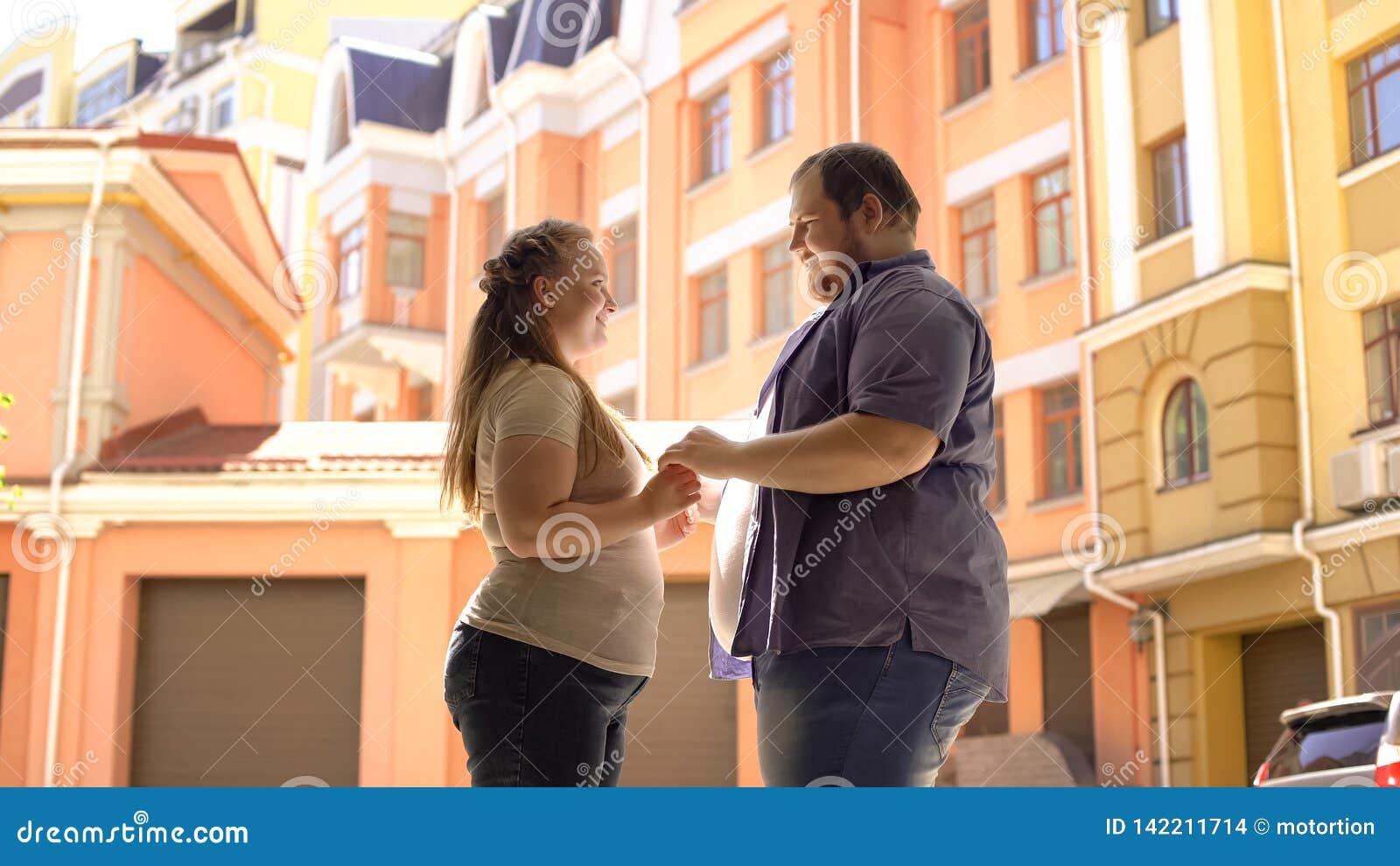 Coppie obese che si tengono per mano, data all aperto romantica, acquisto del bene immobile, gioia