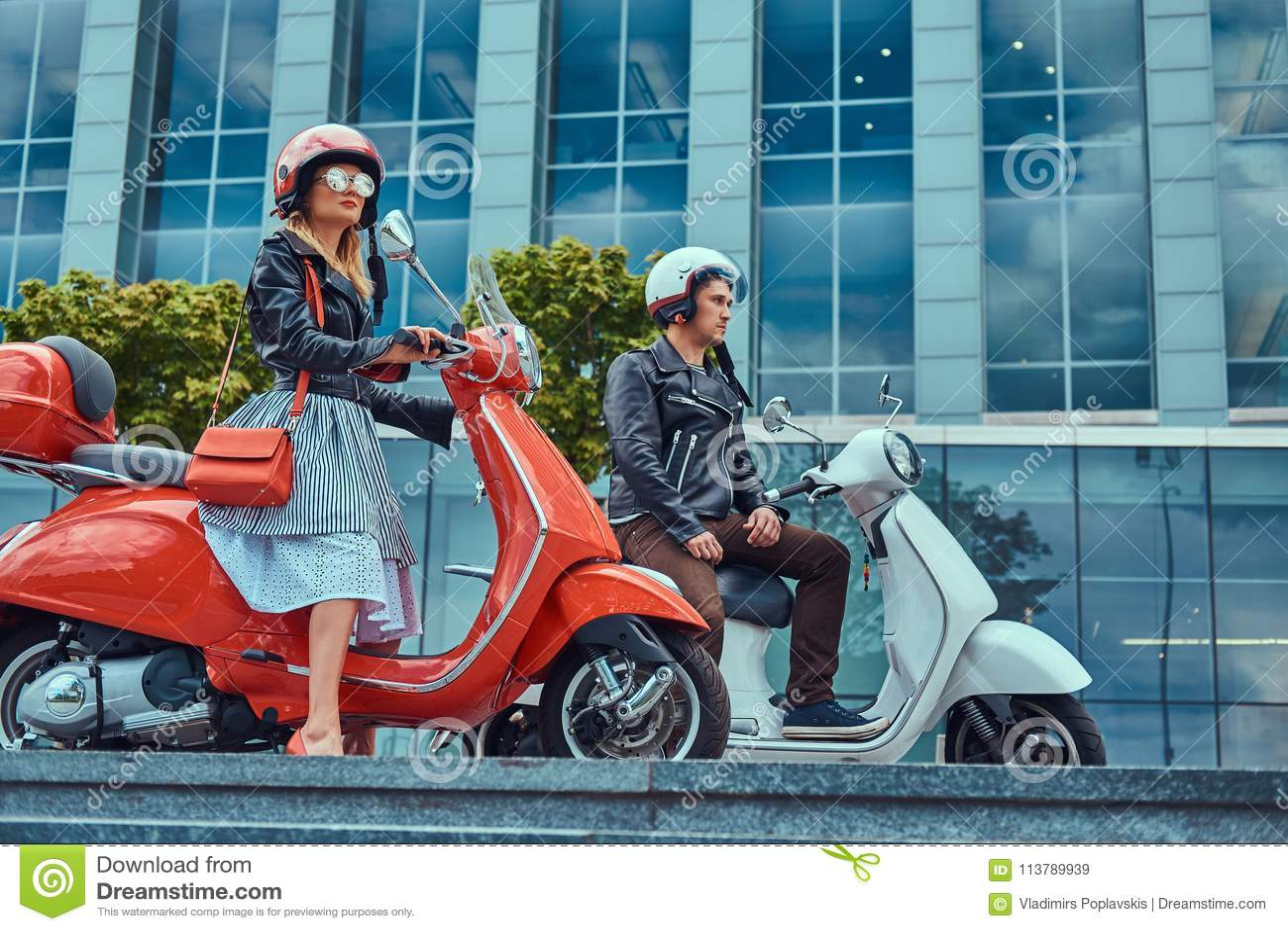 Coppie romantiche attraenti, un uomo bello e femmina sexy, sedentesi sui retro motorini italiani contro un grattacielo