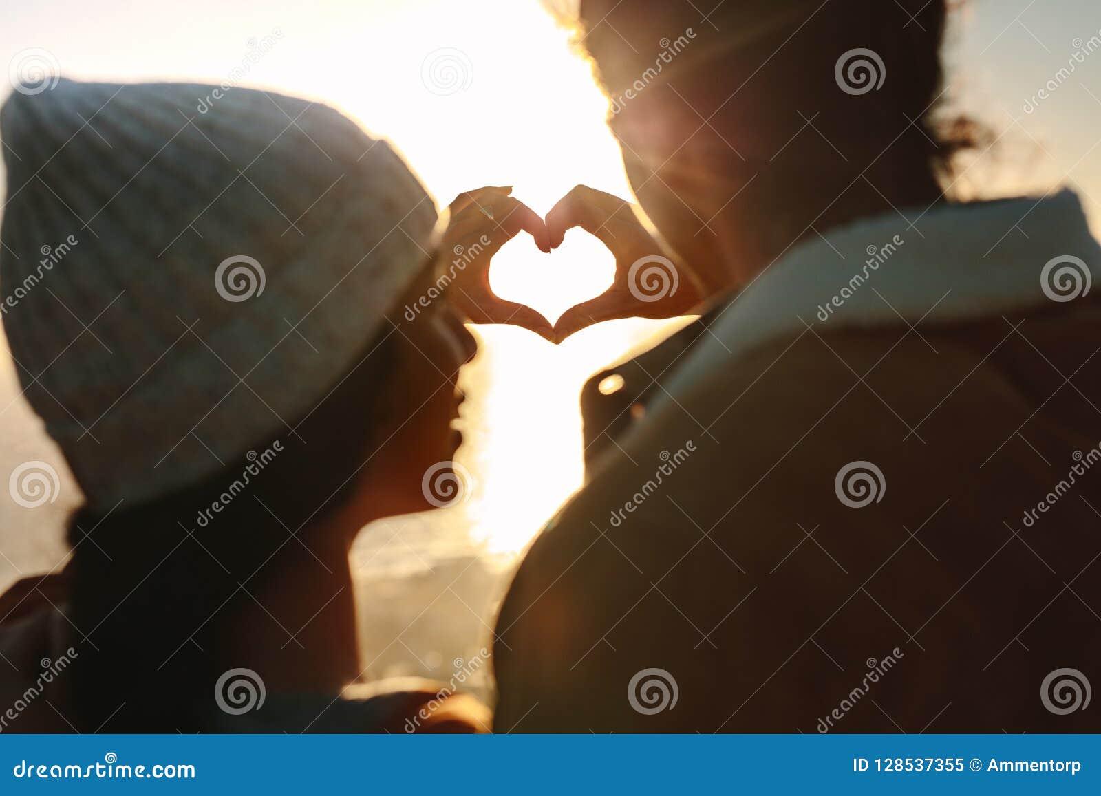 Coppie romantiche che fanno cuore con le mani