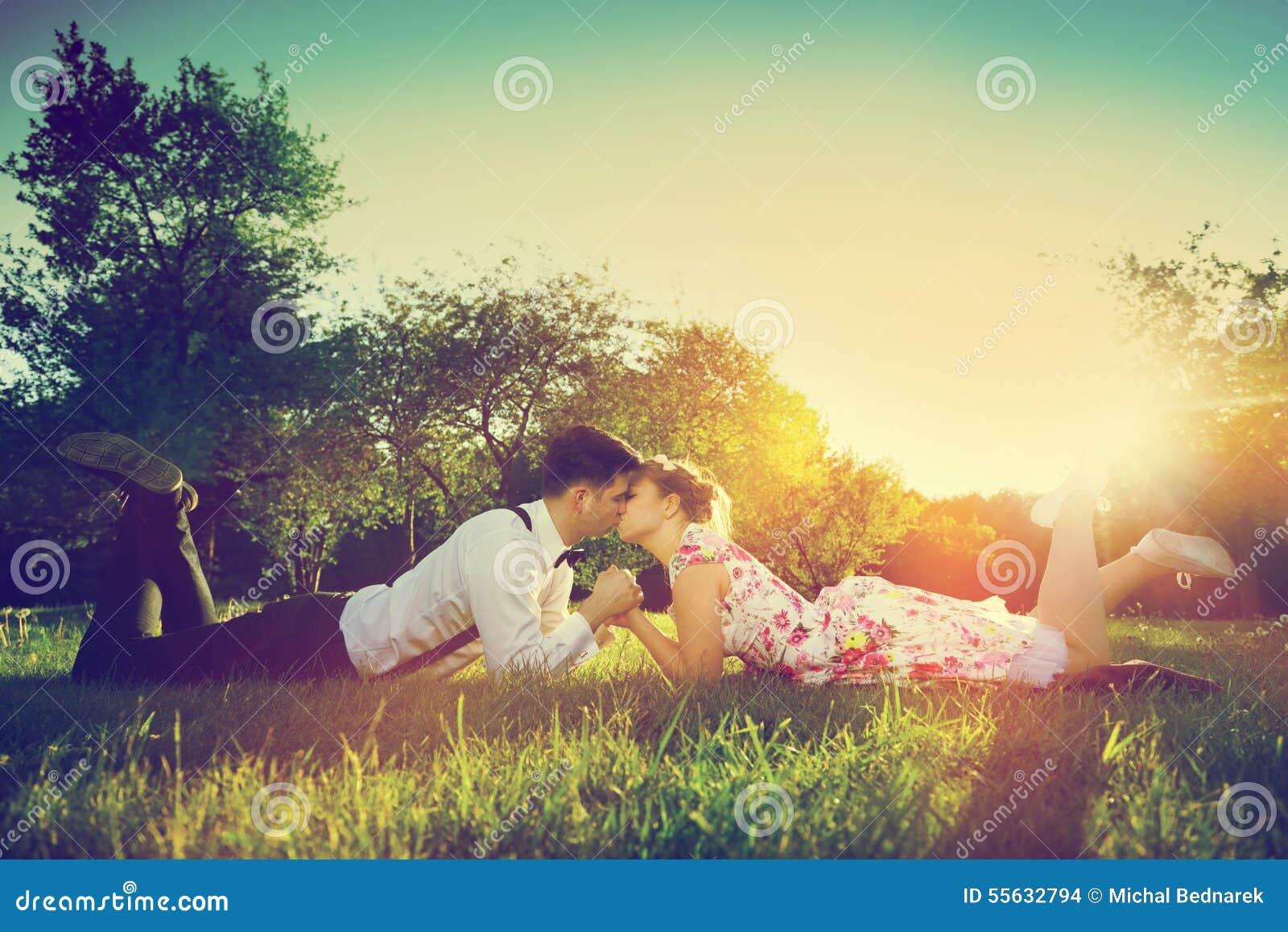 Coppie romantiche nell amore che bacia mentre trovandosi sull erba annata