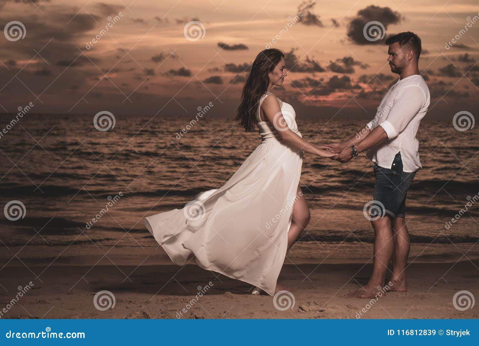 Coppie romantiche sulla spiaggia del Th durante il tramonto