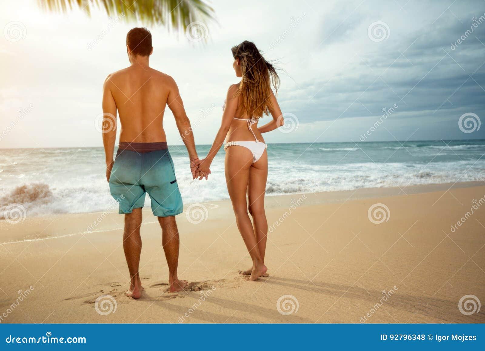 Coppie romantiche sulla spiaggia di tramonto