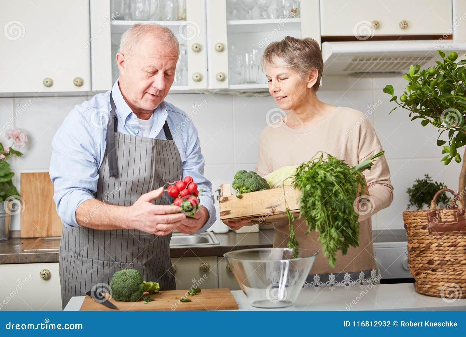 Coppie senior che cucinano pasto vegetariano