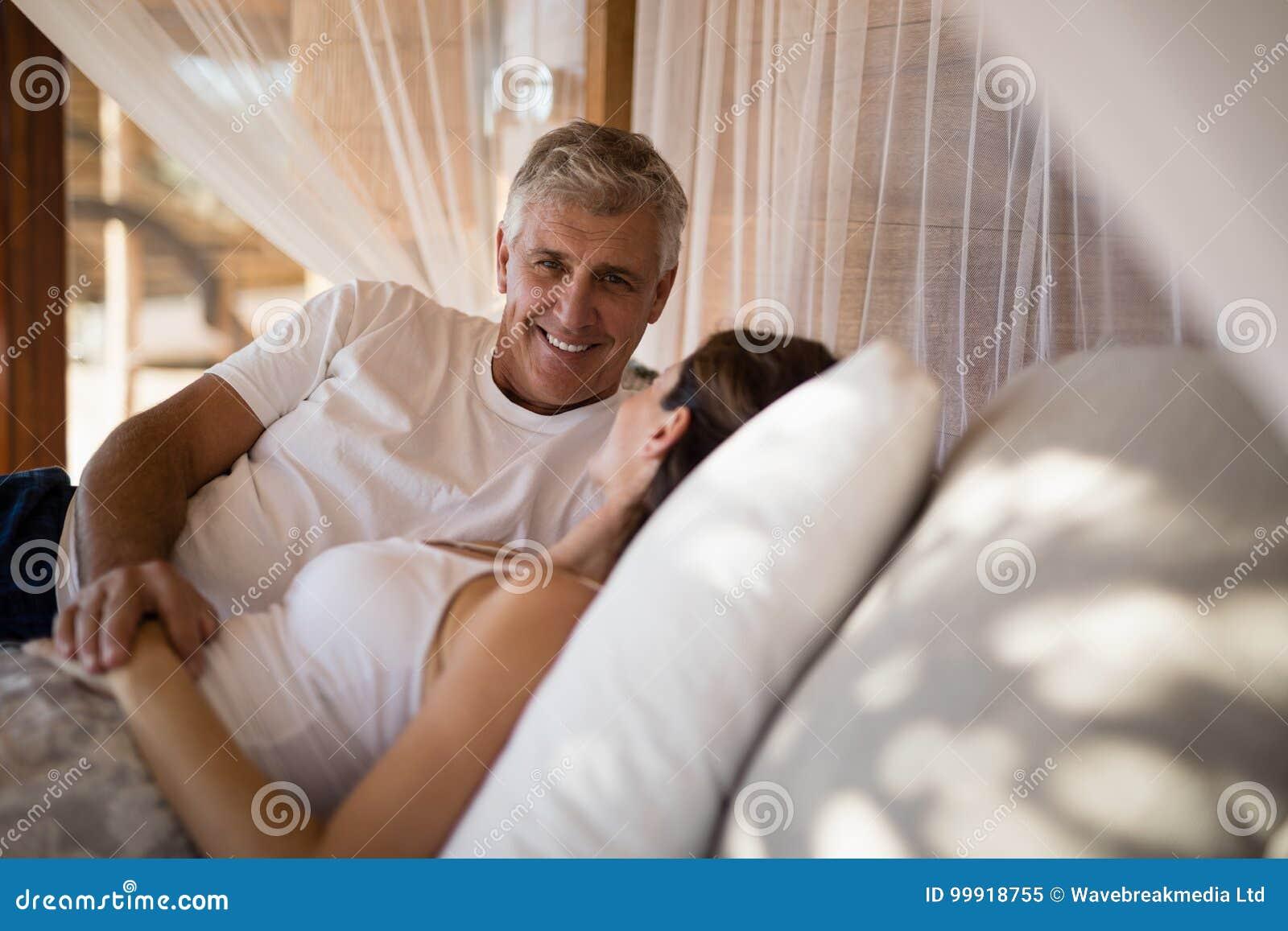 Coppie senior che dormono sul letto del baldacchino