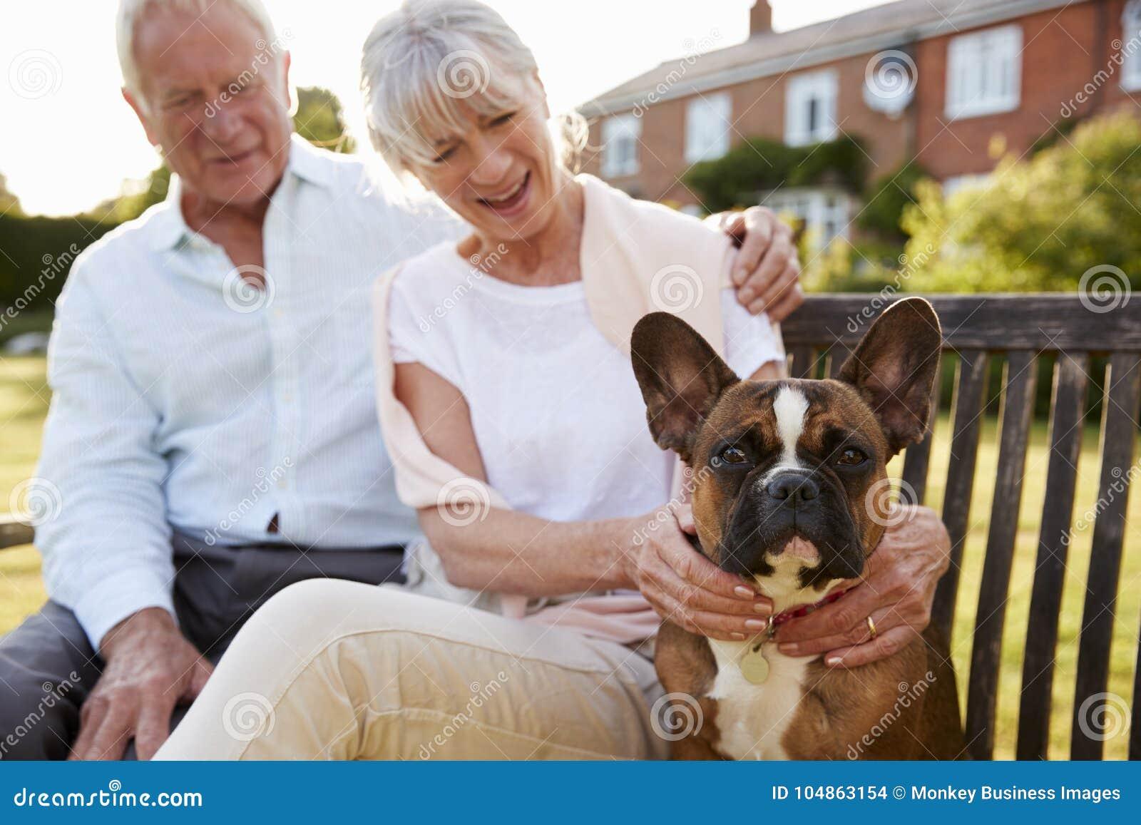 Coppie senior che si siedono sul banco del giardino con il bulldog francese dell animale domestico