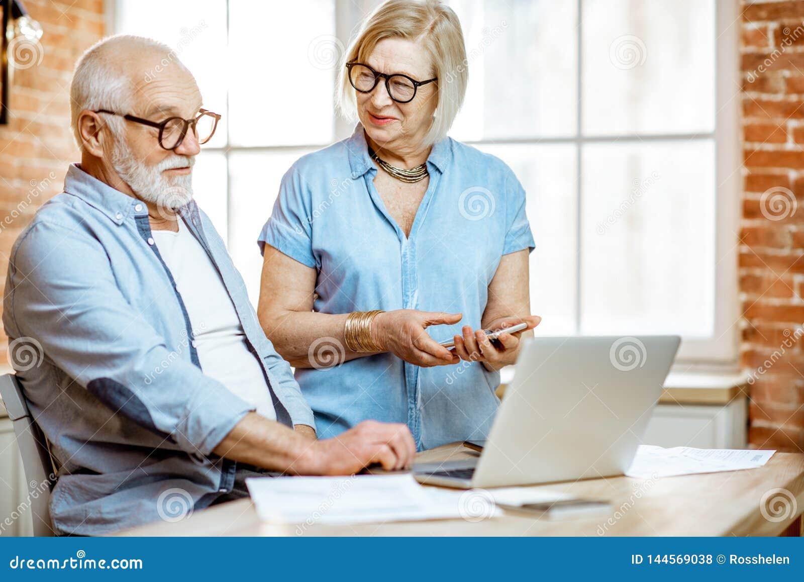 Coppie senior con il computer portatile a casa