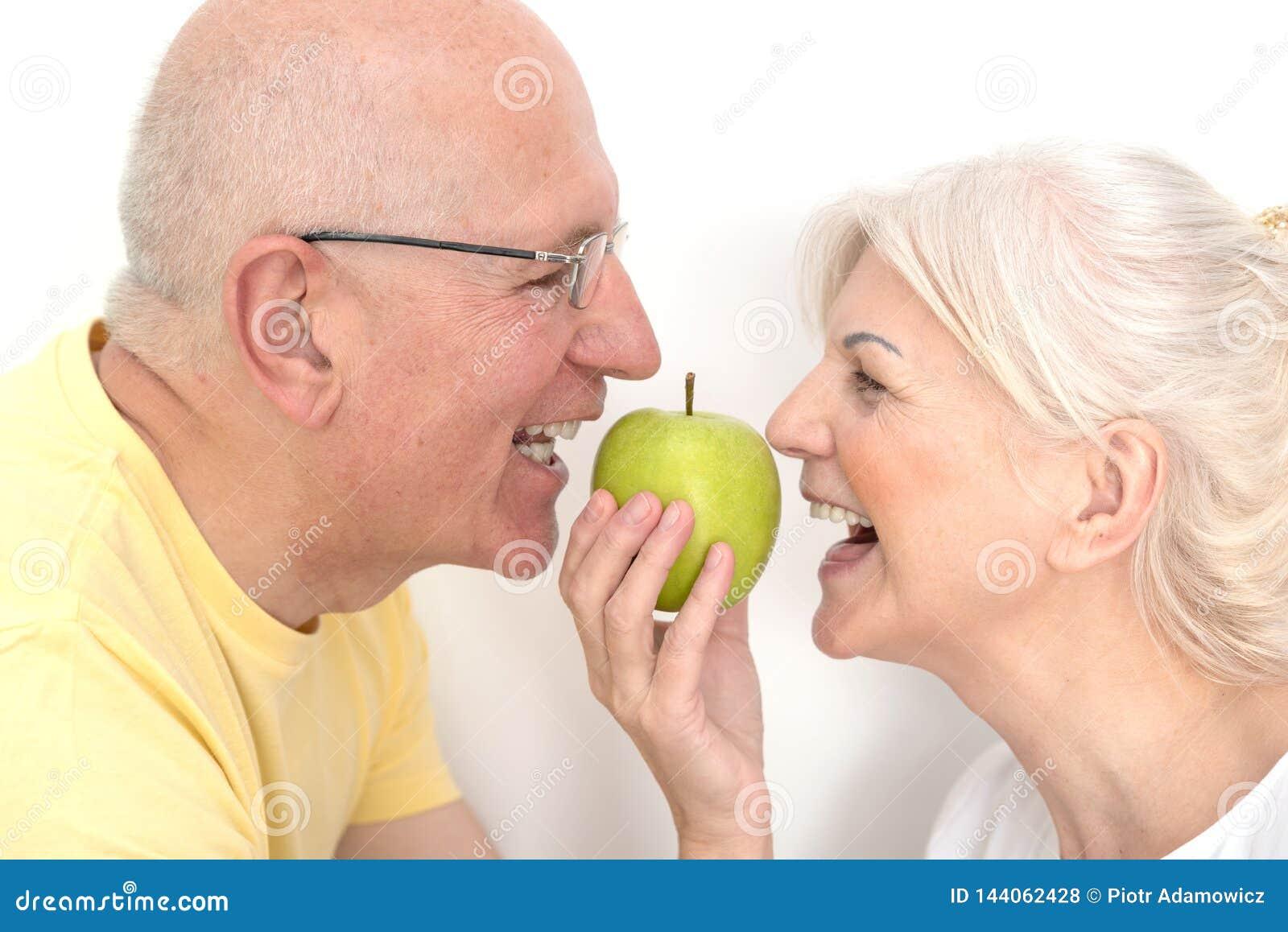 Coppie senior con la mela, concetto sano dei denti