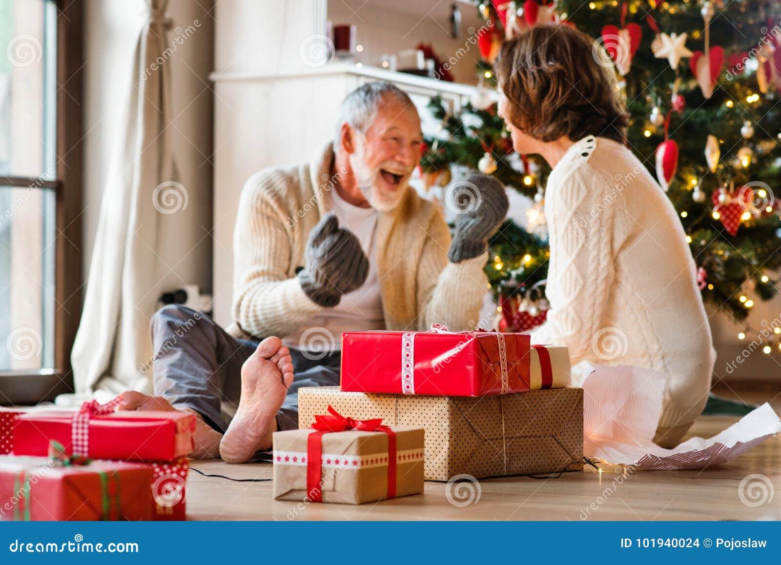 Coppie senior davanti all albero di Natale che gode dei presente
